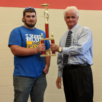Student is presented with car show trophy on Student Appreciation Day.