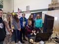 Female 8th grader seated, working on an excavator simulator as other students stand around her watching