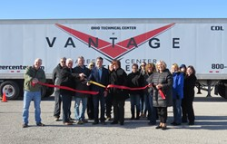 Male and female adults at ribbon cutting in front of a Vantage semi tractor trailer