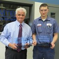 Supt Rick Turner with male Industrial Mechanics student holding etched acrylic nameplates