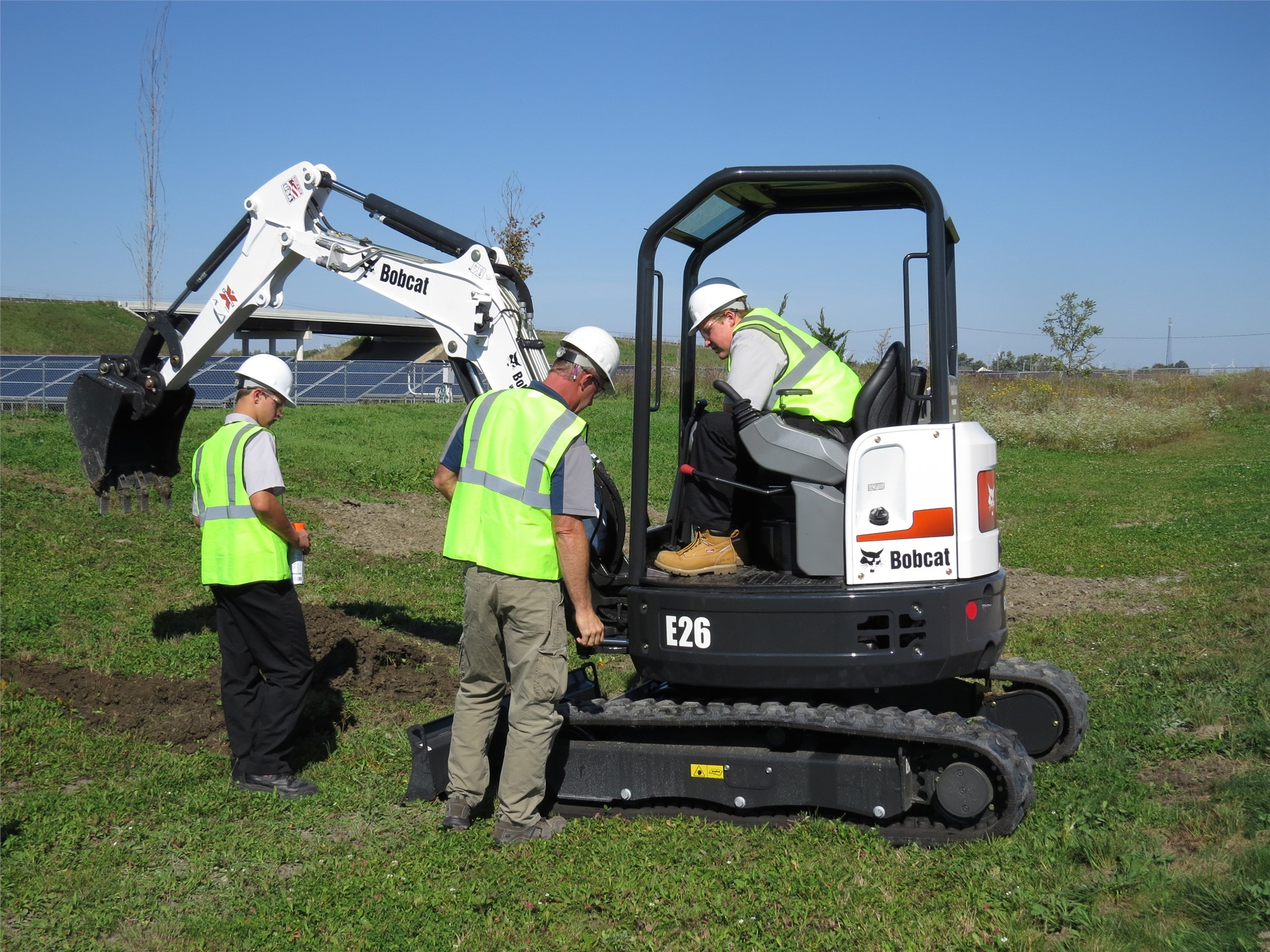 Students using Bobcat while instructor watches