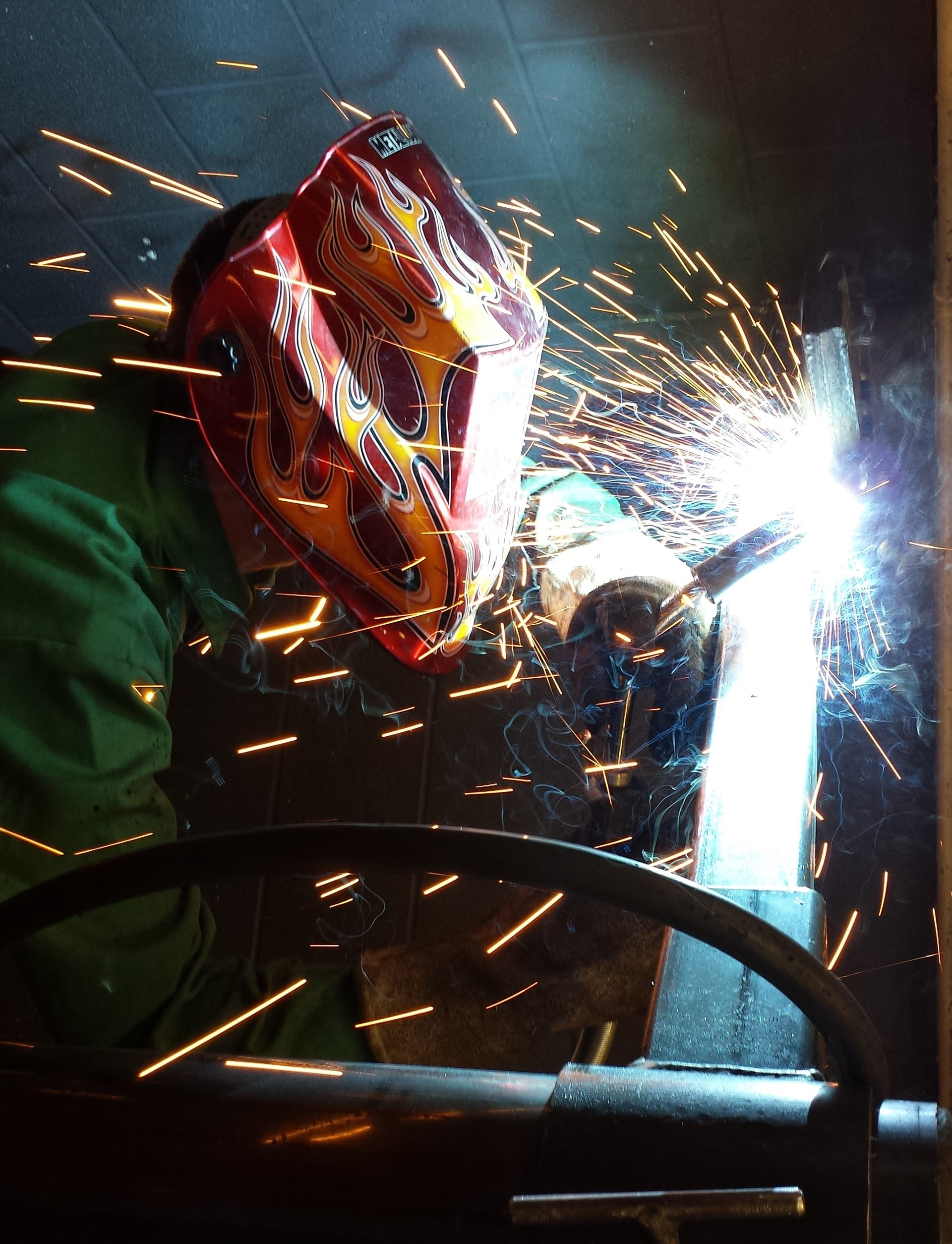 Welder wearing yellow and orange flames helmet and sparks flying