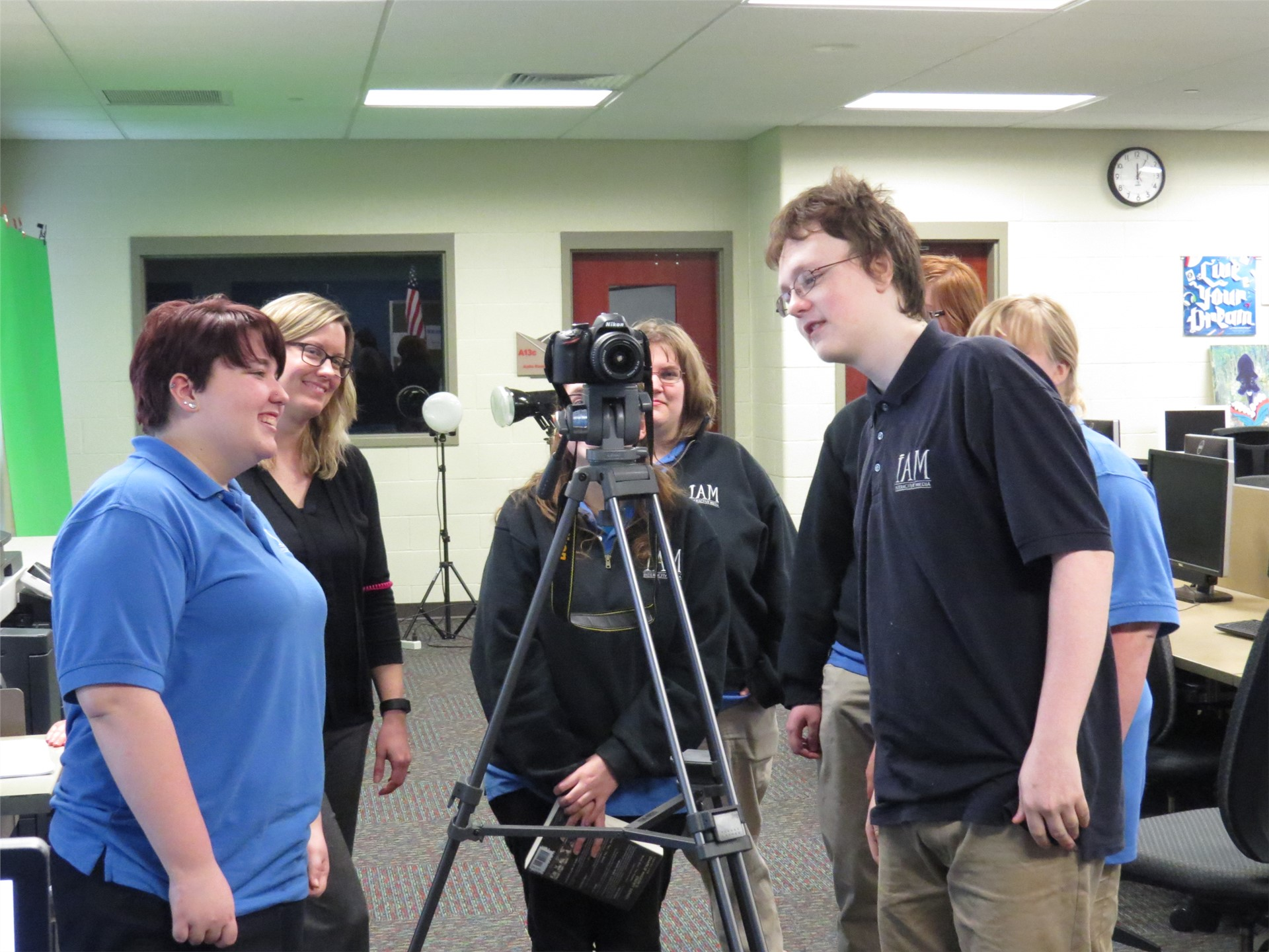 Male & female Interactive Media students standing around a tripod and camera