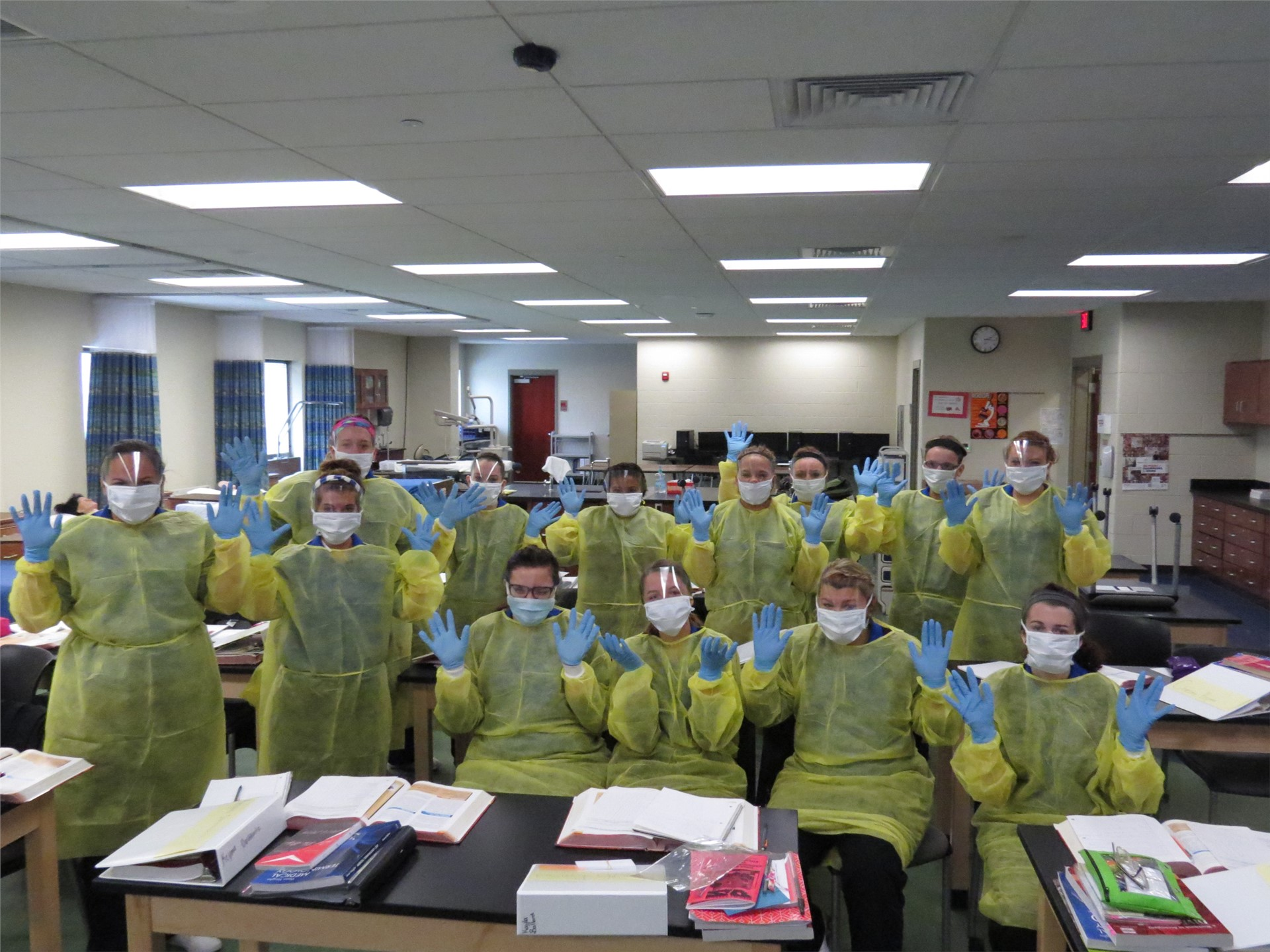 A large group of Health Technology students dressed in yellow protective gowns, blue gloves, and whi
