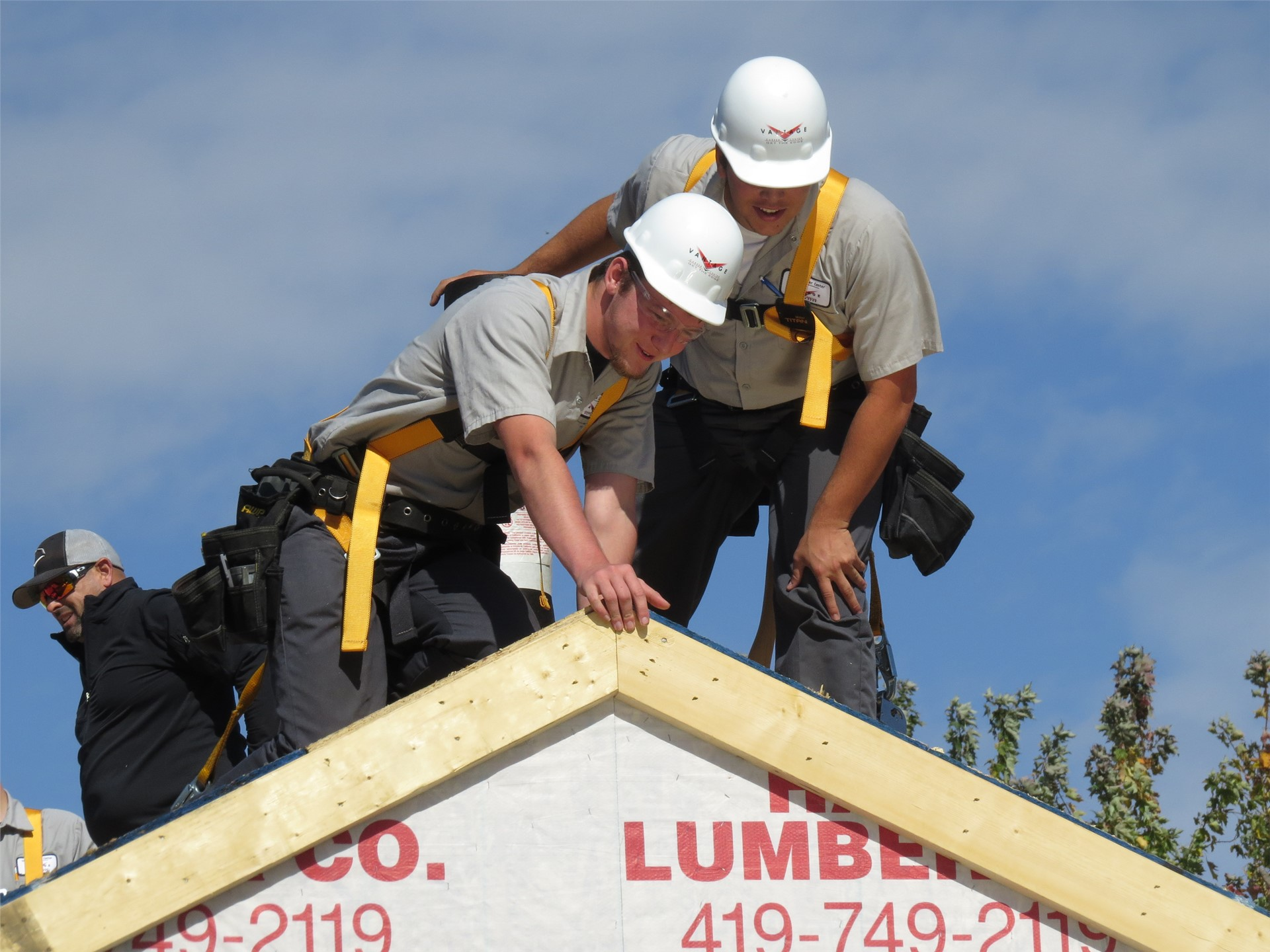 2 male Carpentry students wearing white hard hats on the roof of a building