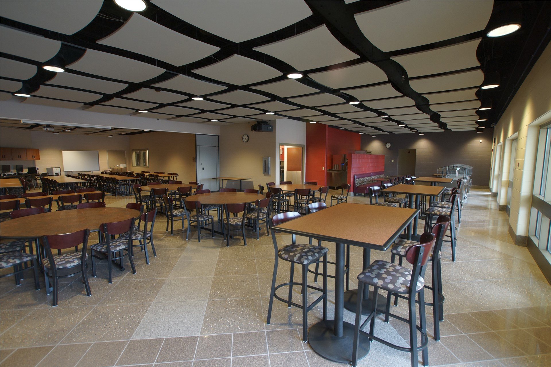 Tables and chairs in empty Cup & Saucer Restaurant.  Drop ceiling tiles.