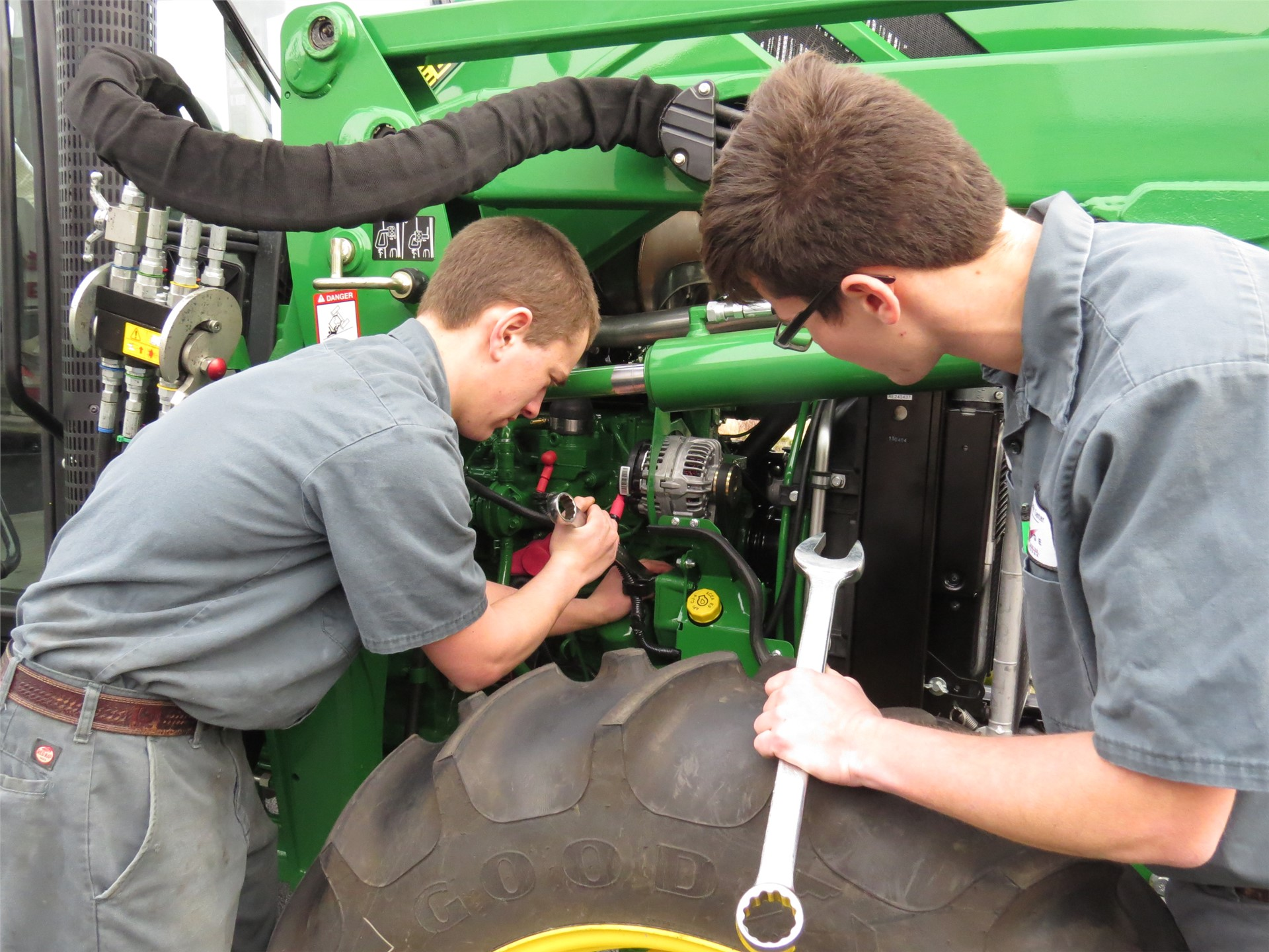 Two male students working on green tractor in the Ag lab