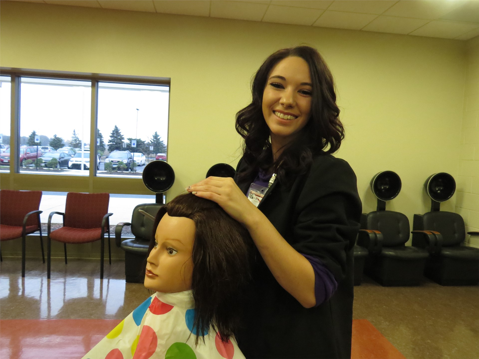 Female Cosmetology student smiling while working on a mannequin