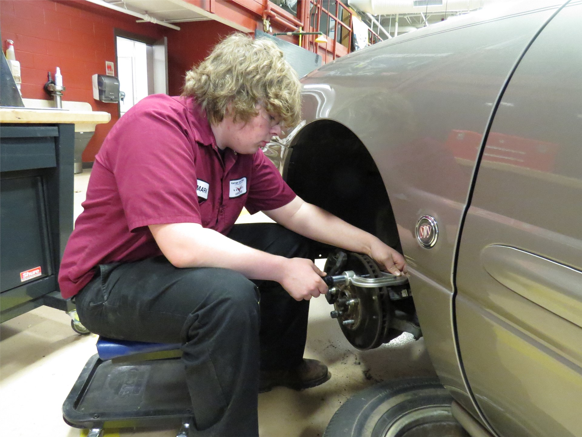 Student working on car brakes