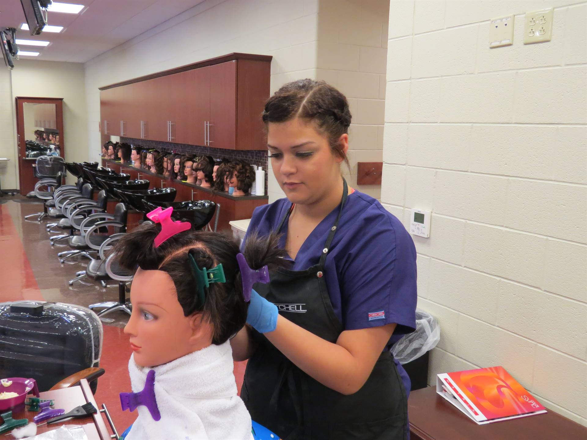 Female cosmetology student working on a mannequin's hair