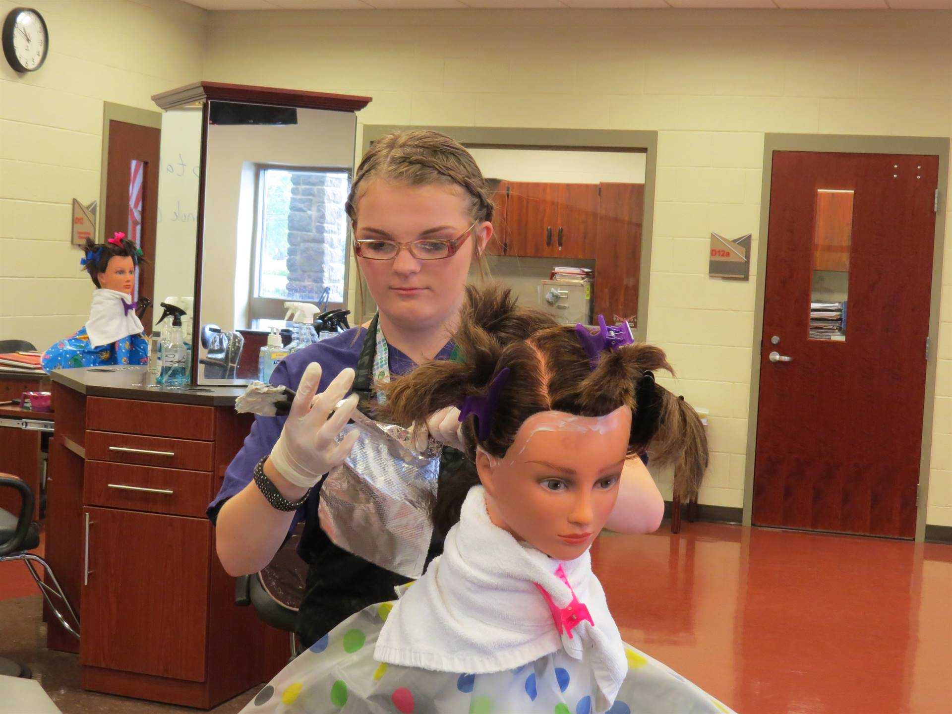 Female cosmetology student coloring a mannequin's hair