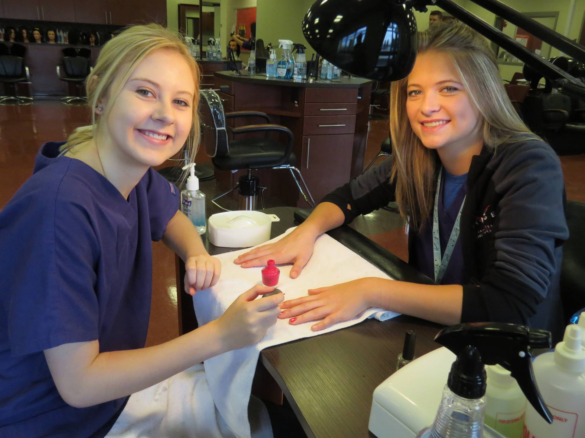 Two female cosmetology students smiling at the nail polish station