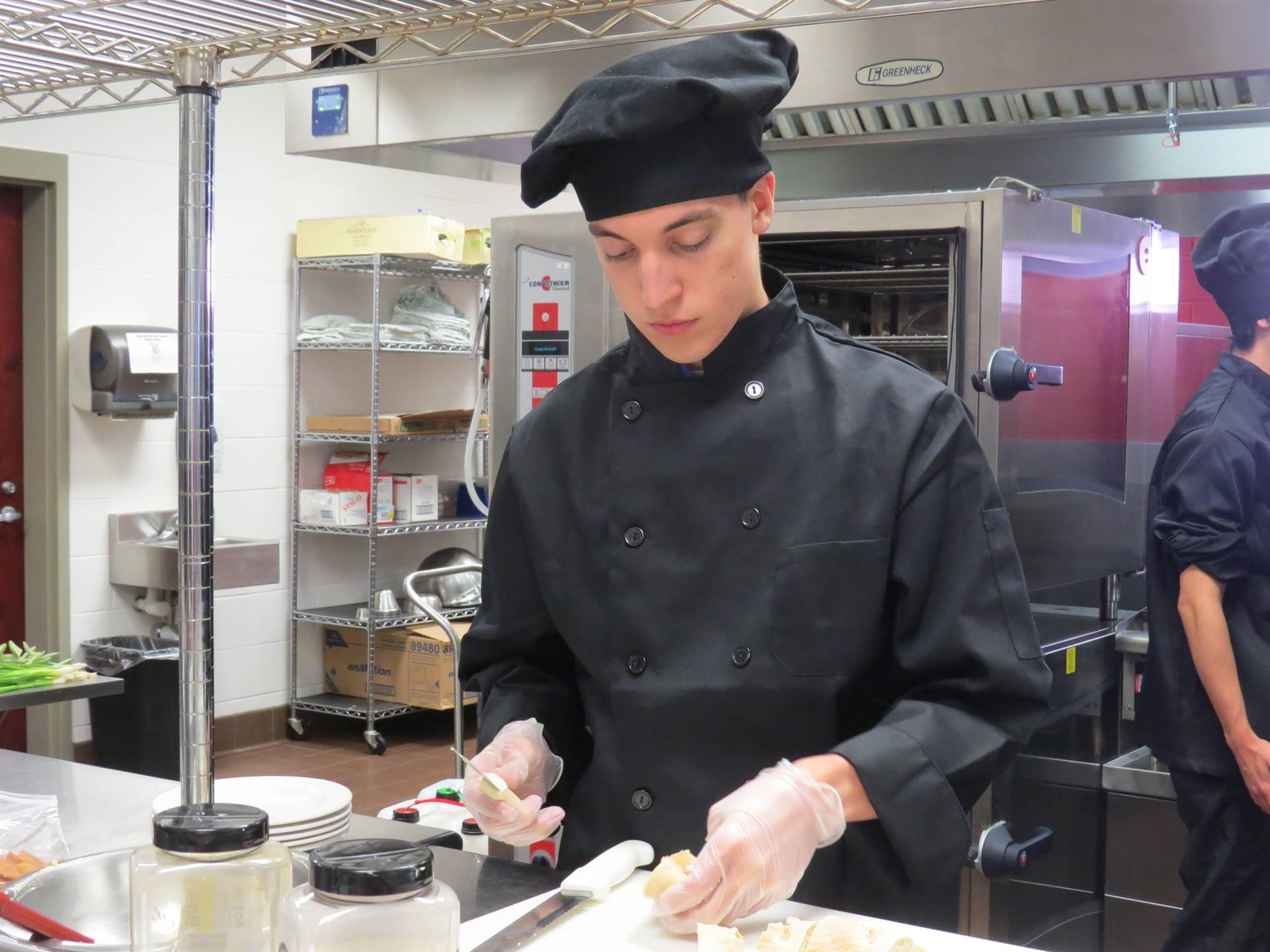 Male culinary arts student cutting food