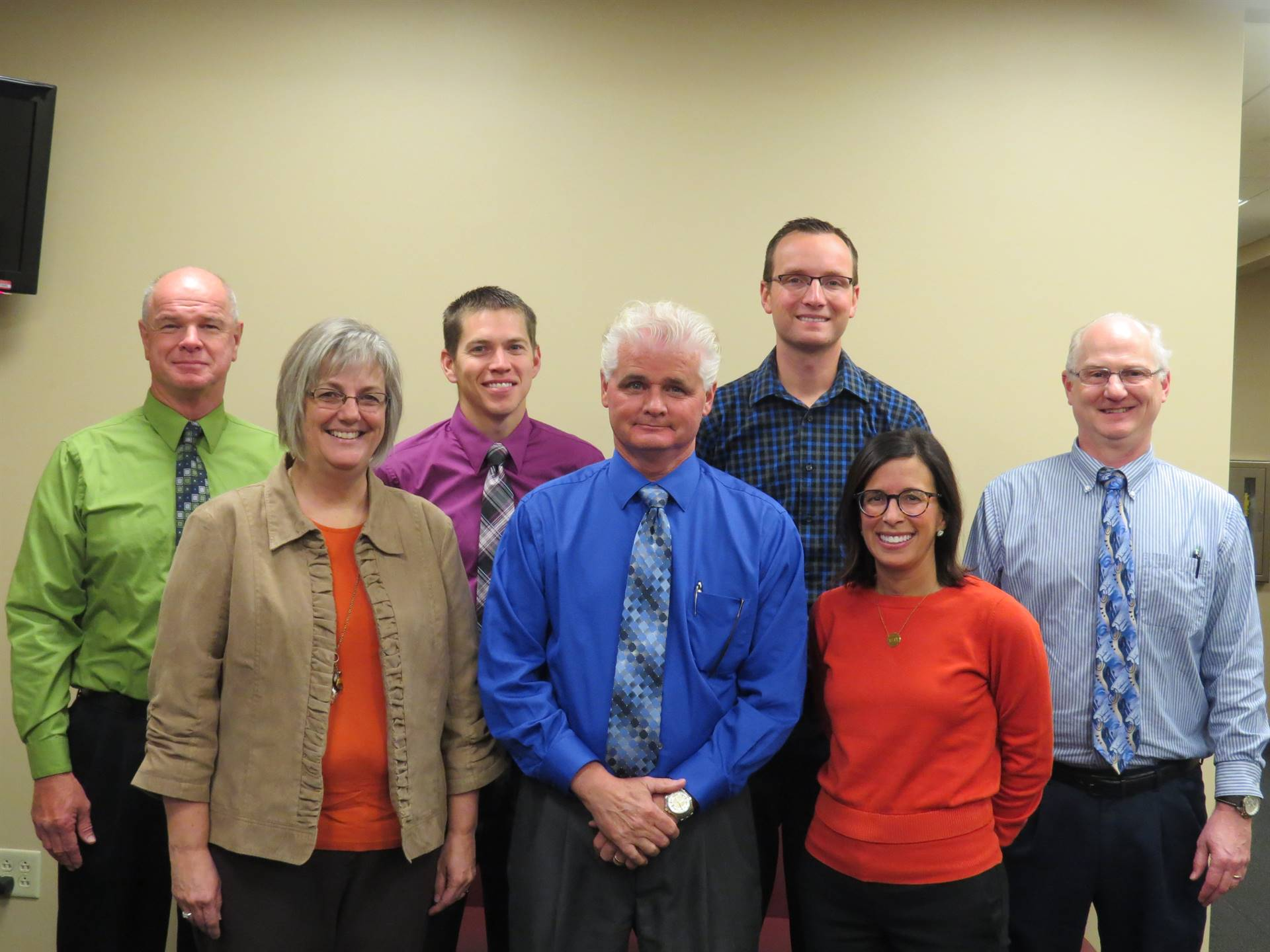 Seven male and female members of the Vantage Administrative team standing and smiling