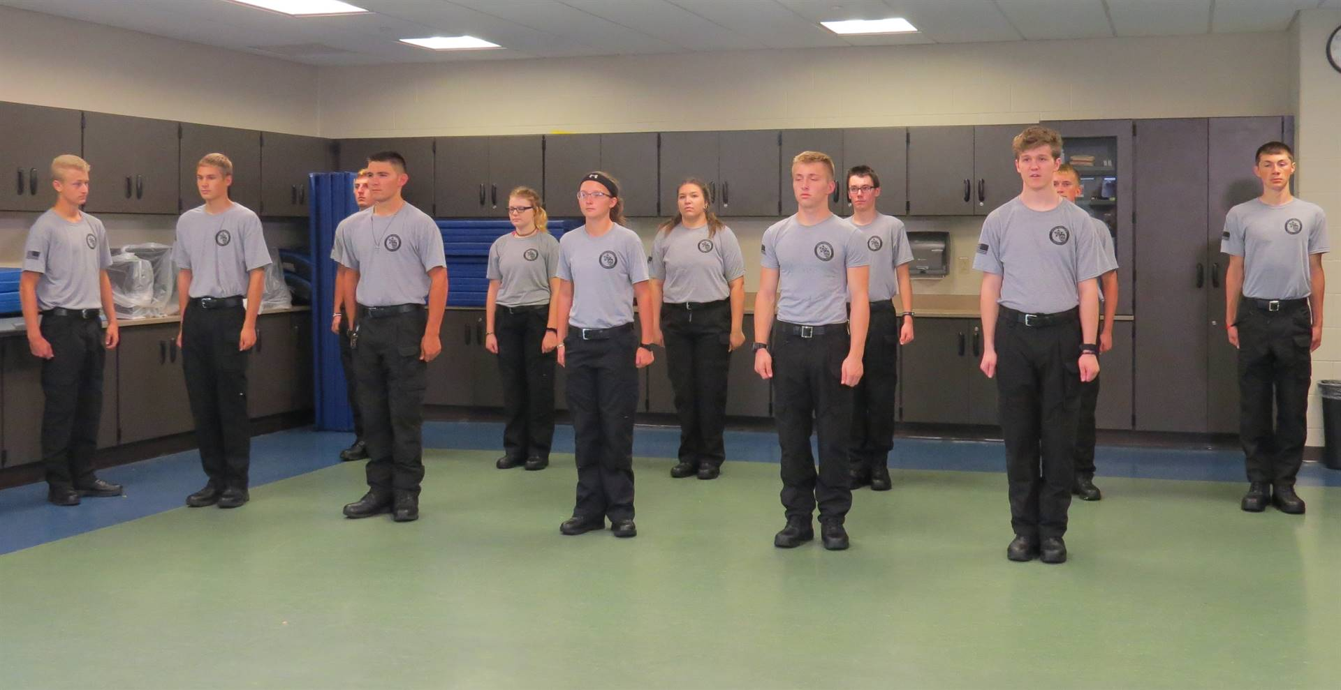 Male & female Criminal Justice students standing at attention