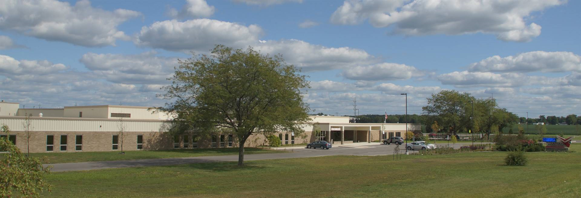 Panoramic picture of the Vantage building with green grass and trees
