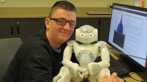 Male Networks Systems student hugging NOW Robot