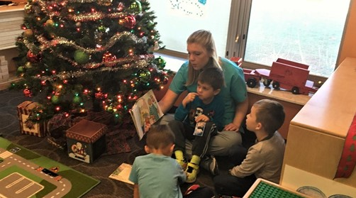 Female student reading a book to 3 toddlers next to the Christmas tree