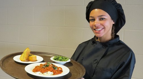 Female culinary arts student displaying food on a tray