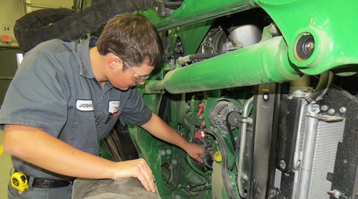 Male Ag student working on a green tractor