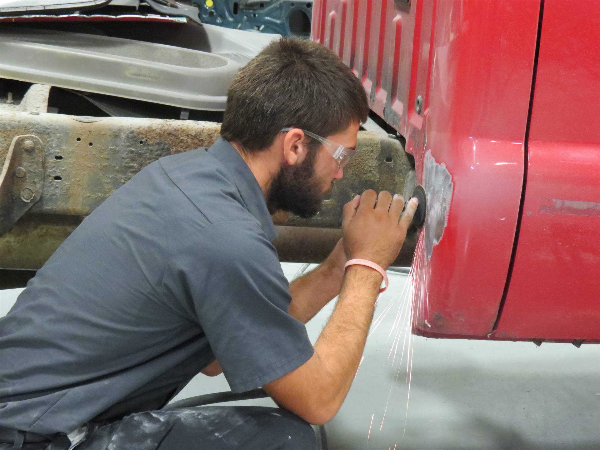 Male Auto Body student grinding down a red pick up truck