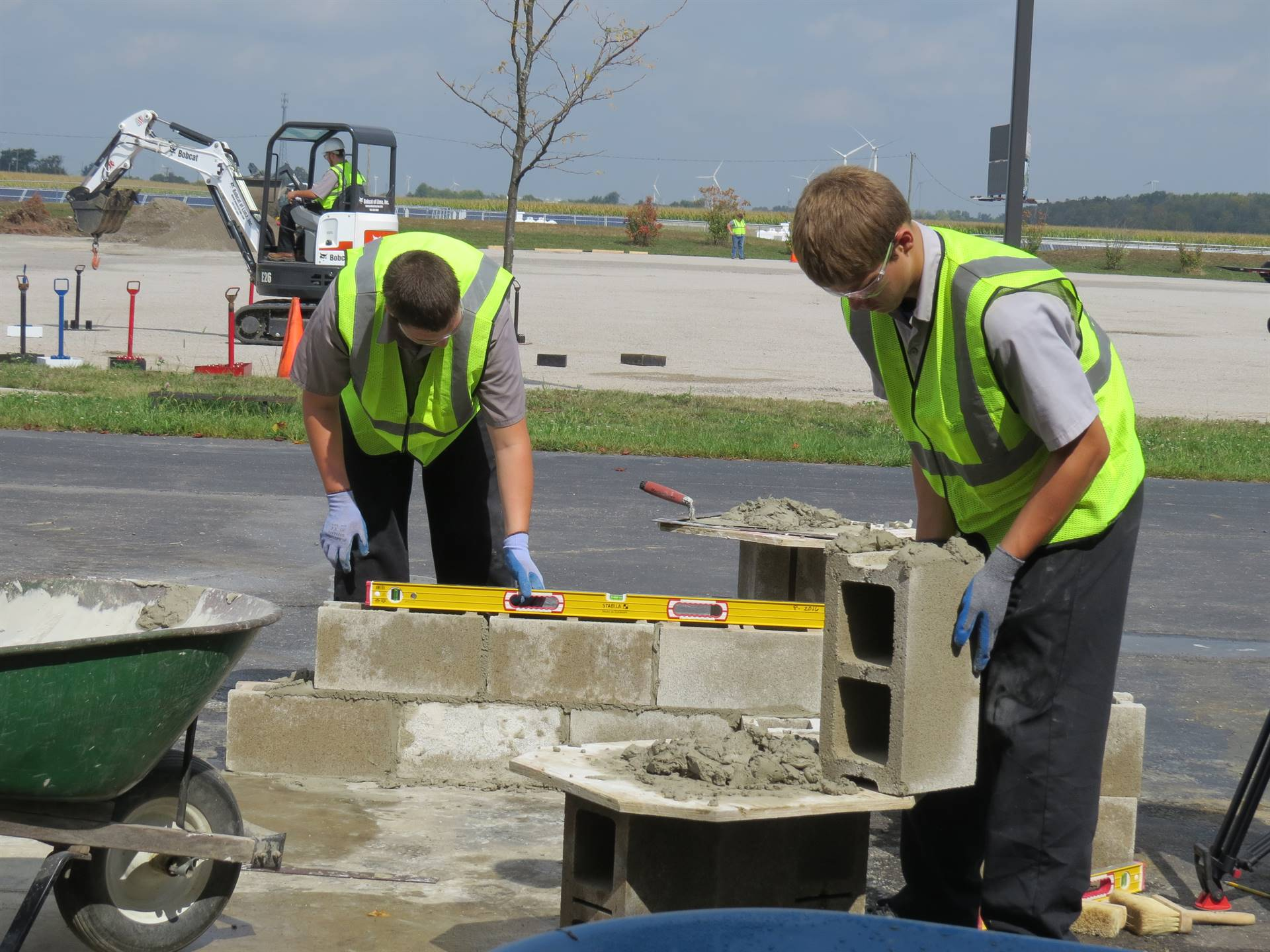 Two male students building a concrete block wall
