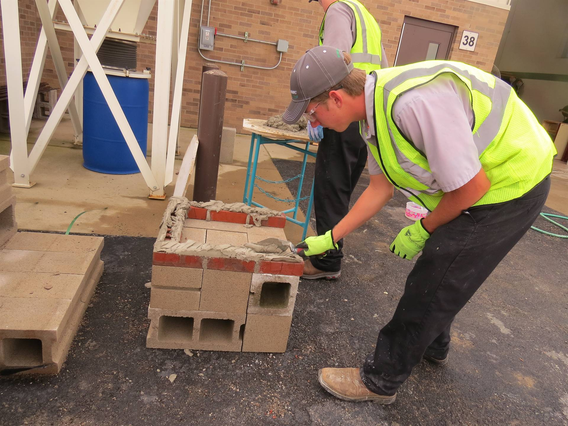 One male student working with brick and mortar