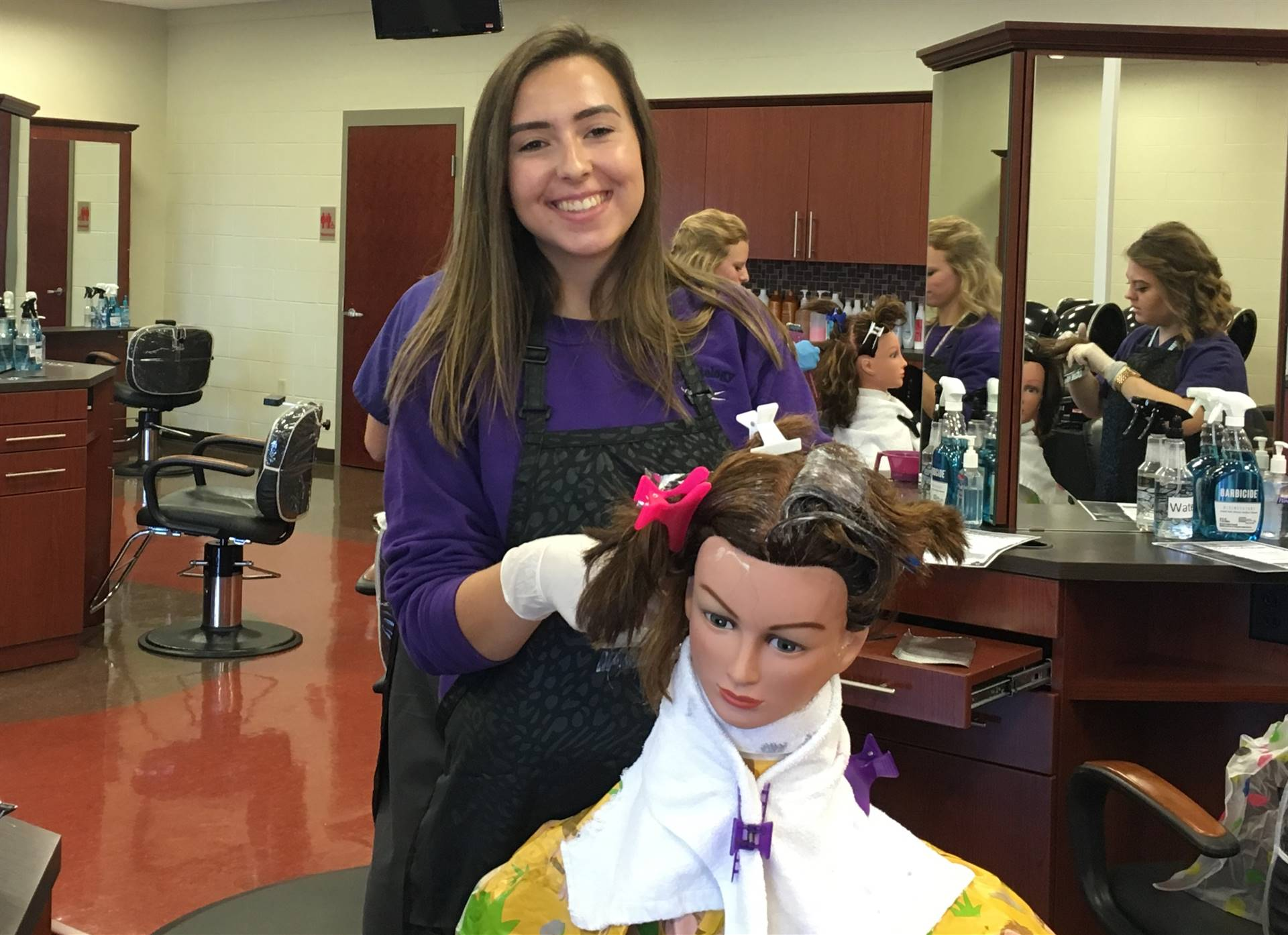 Smiling female Cosmetology student working on a mannequin
