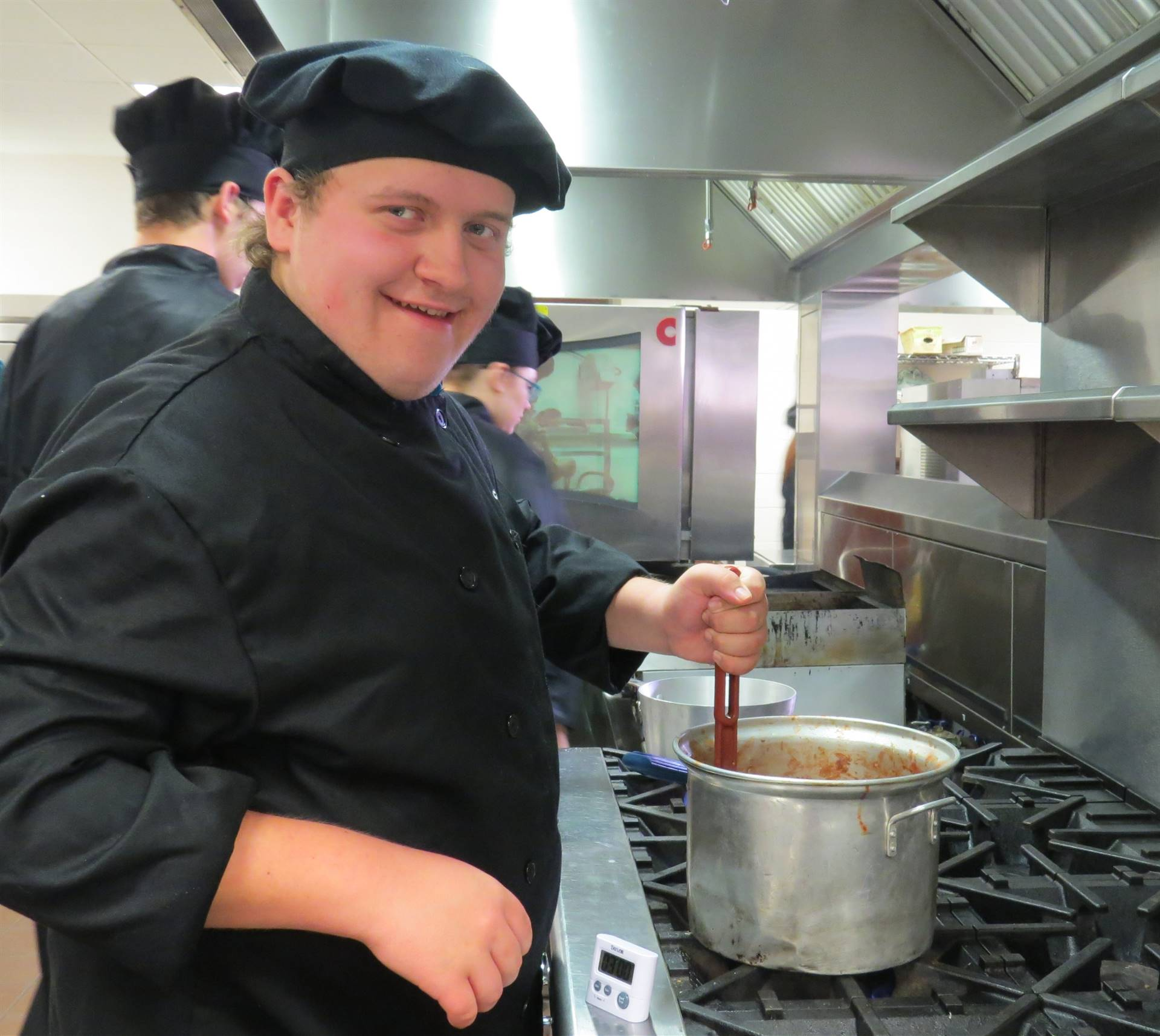 Male Culinary Arts student in black chef coat and hot stirring a pot on the gas stove