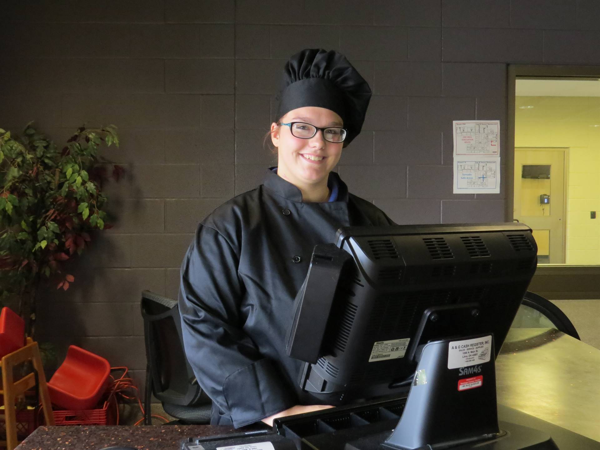 Female Culinary Arts student in black chef coat and hat at the cashier station