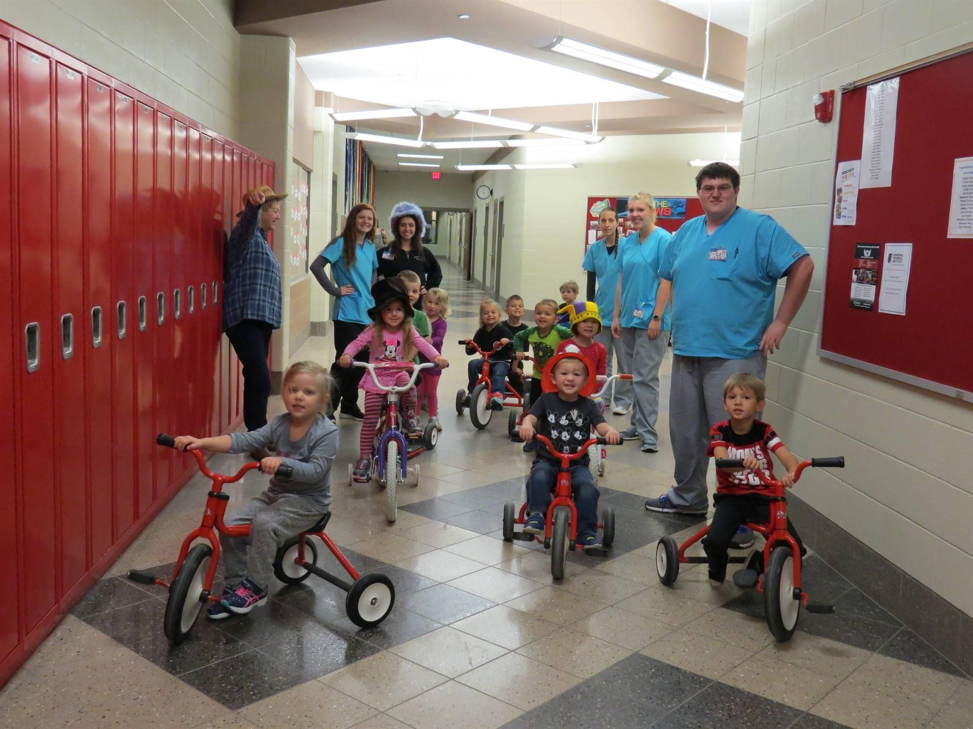 Preschoolers wearing hats on trikes in the school hallway with students