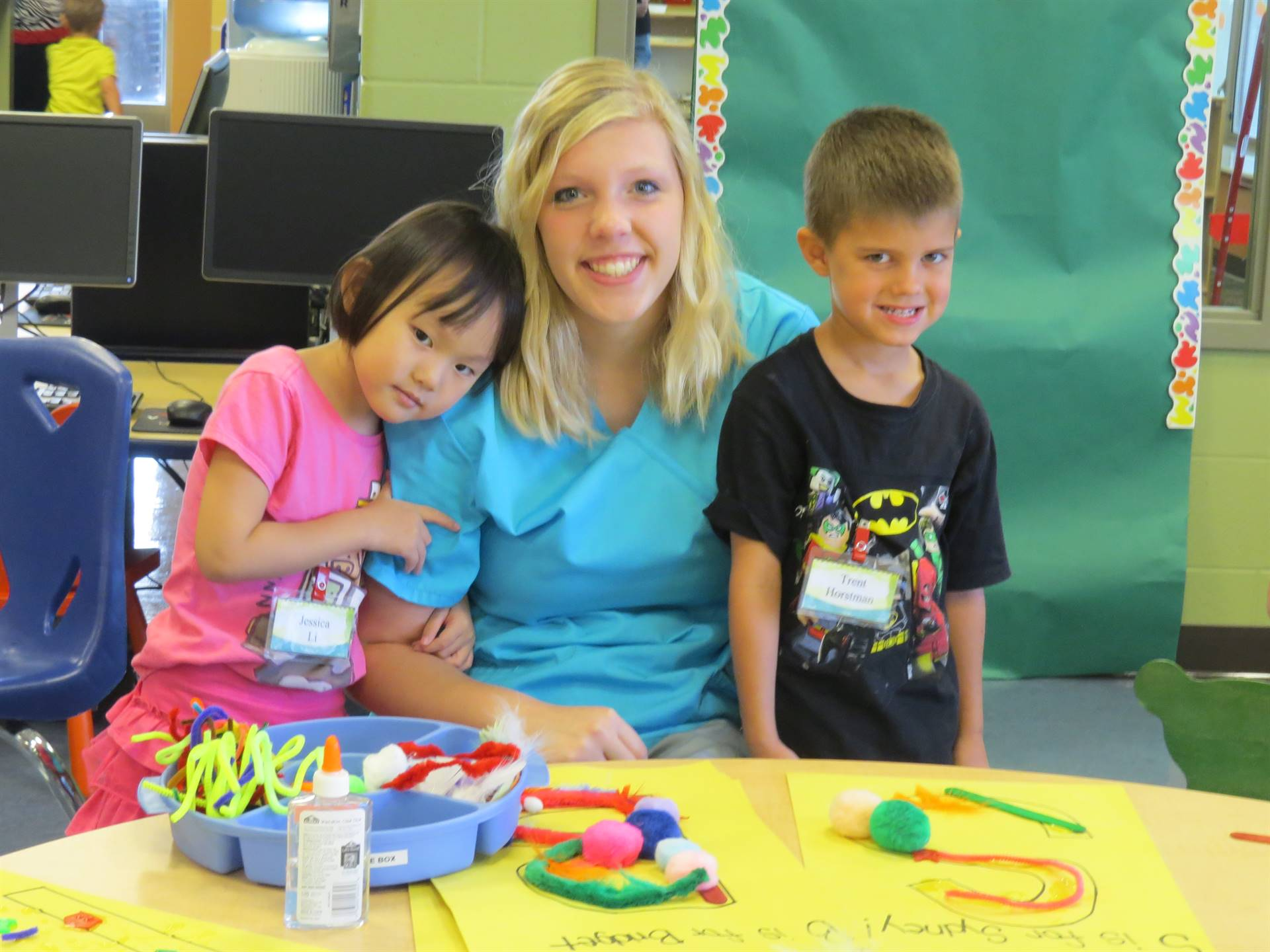 A smiling female Early Childhood Education student with a preschooler on each side of her