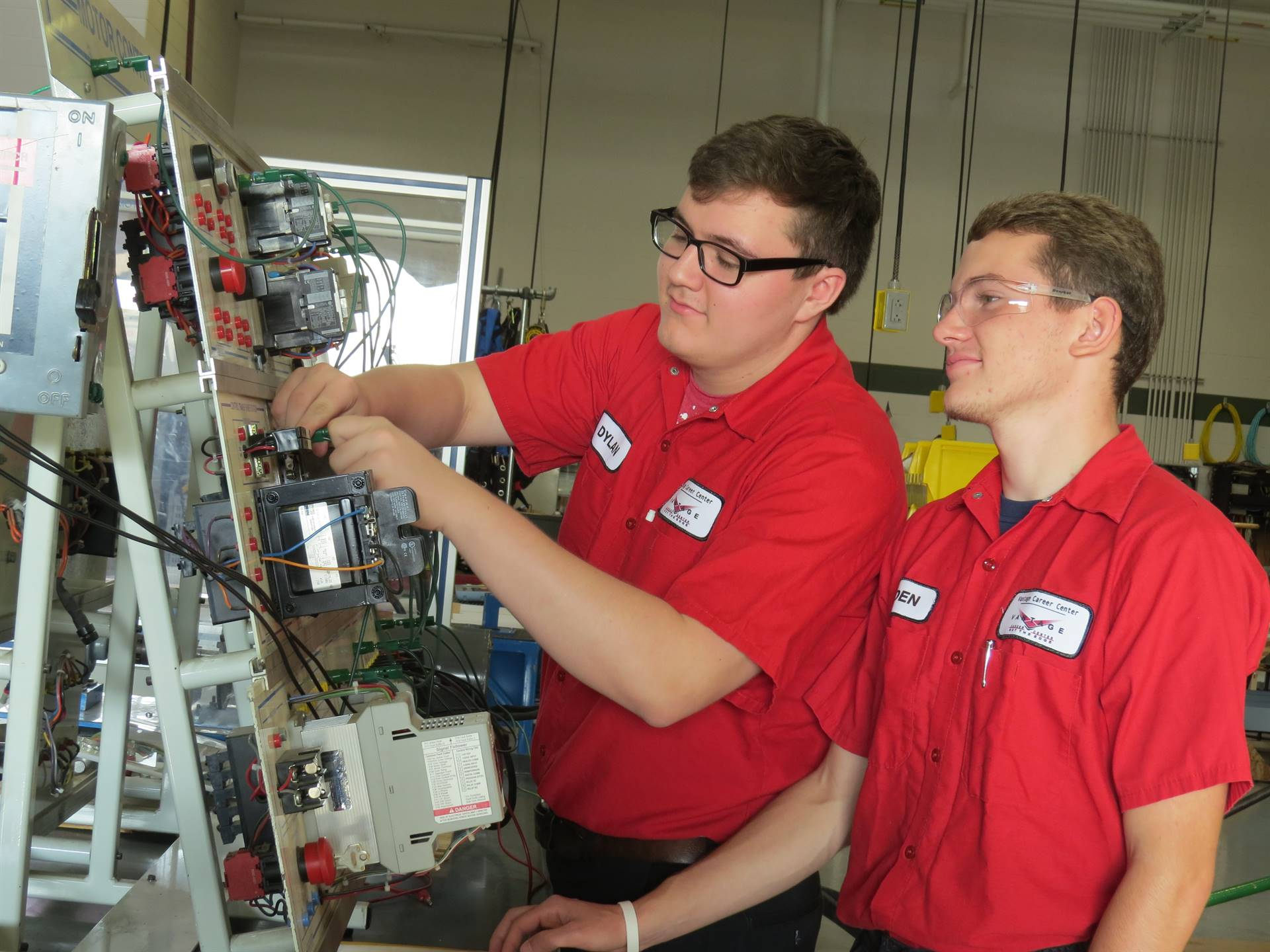 Two male Electricity students working on a large electronic board