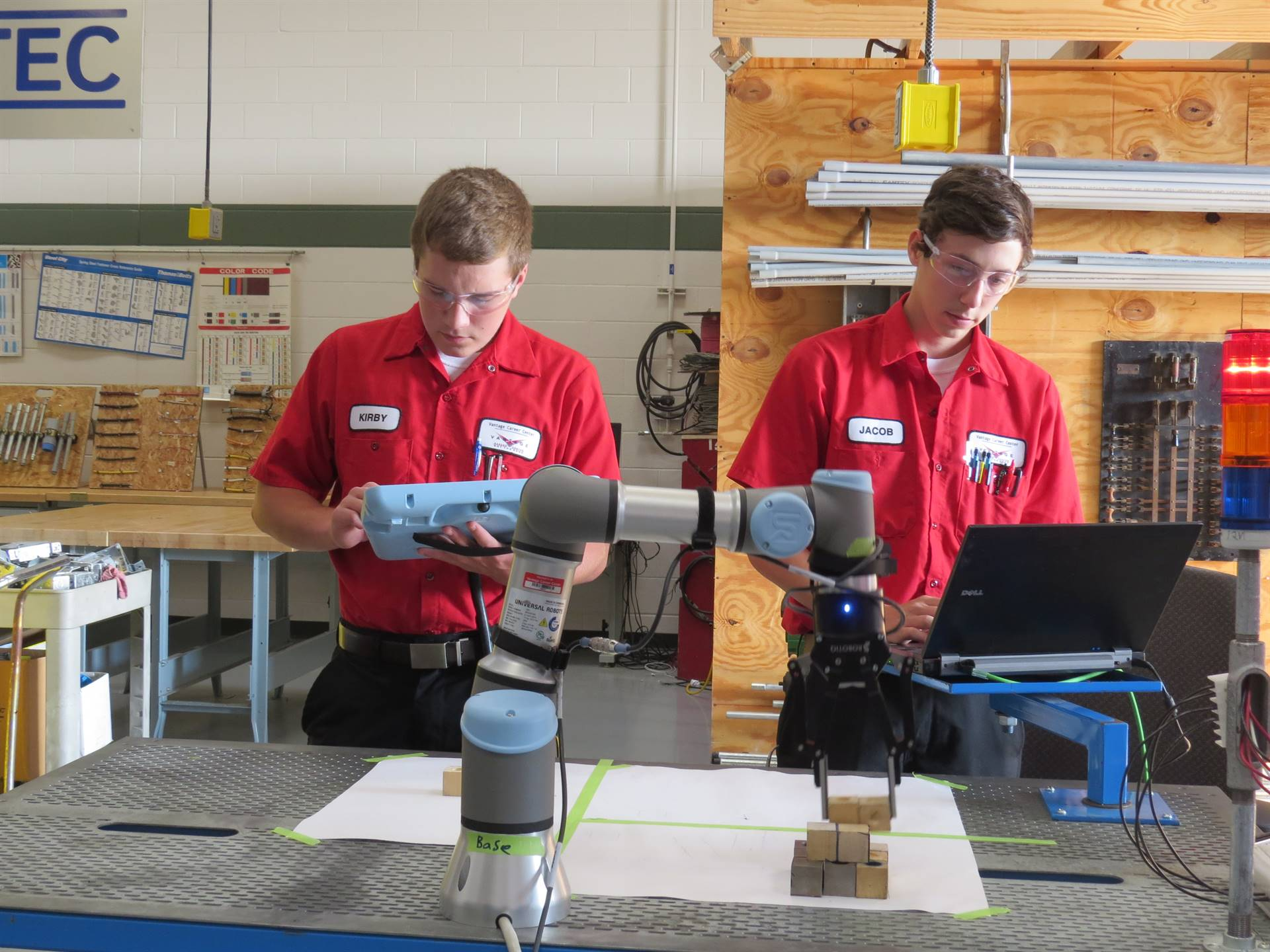 Two male Electricity students programming a robotic arm
