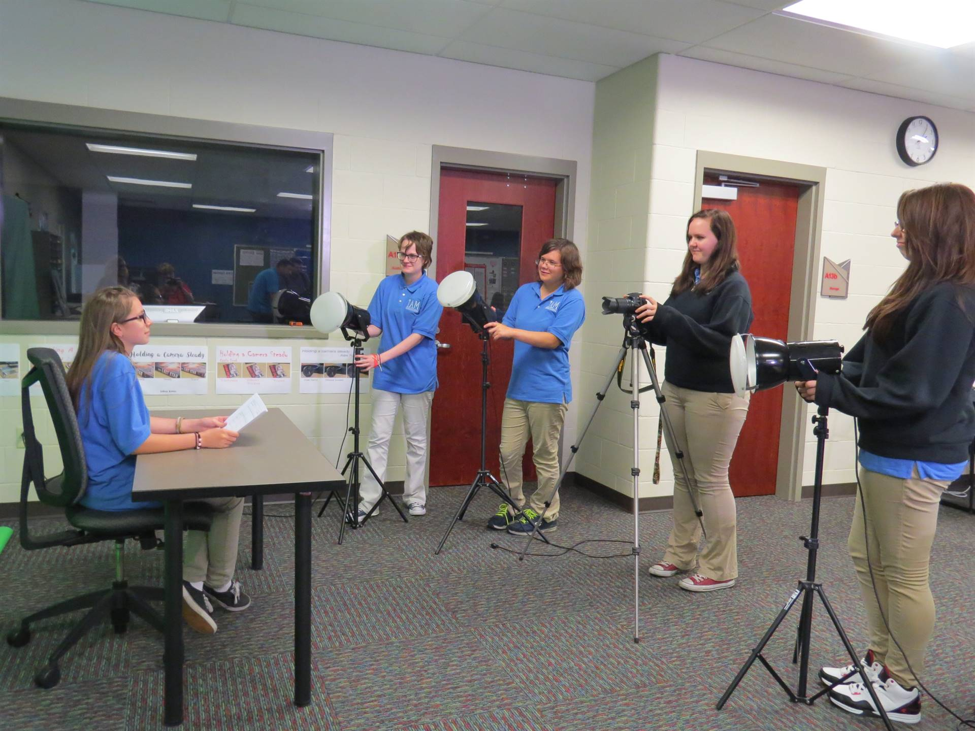 Five female Interactive Media students setting up a newscast using lights and green screen