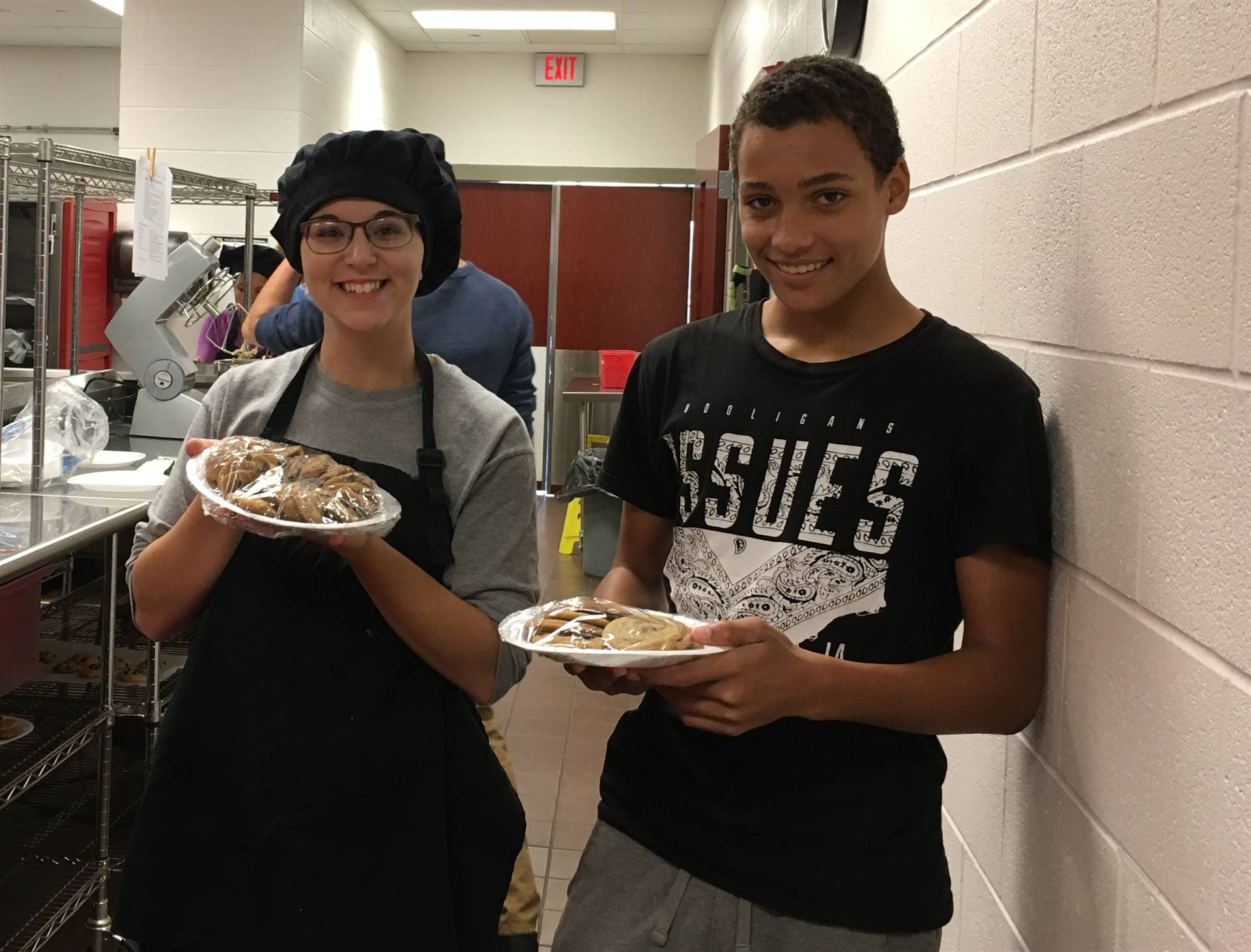 Female and male Culinary Arts students smiling with plates of food