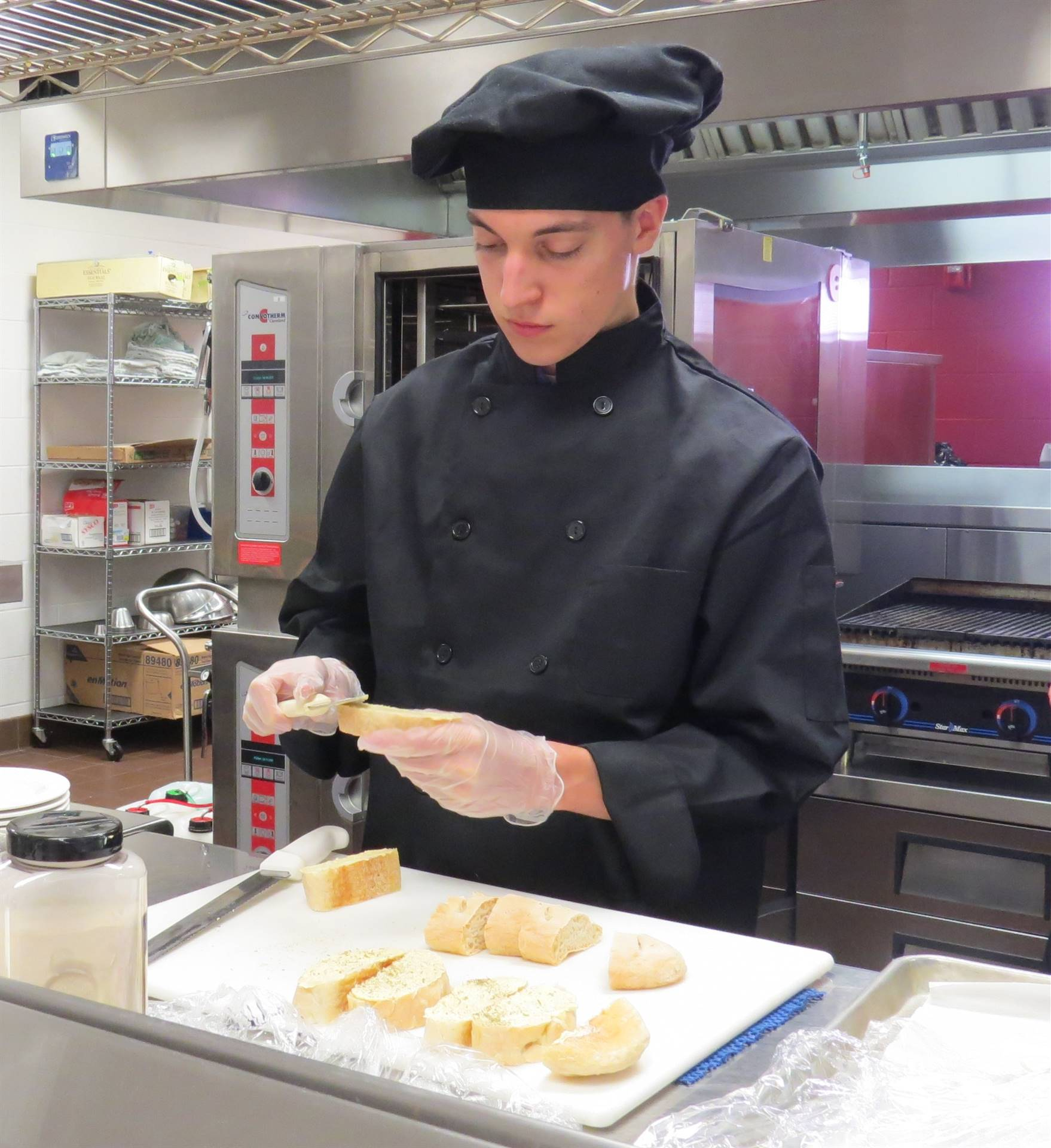 Male Culinary Arts student in black chef coat and hat buttering garlic bread