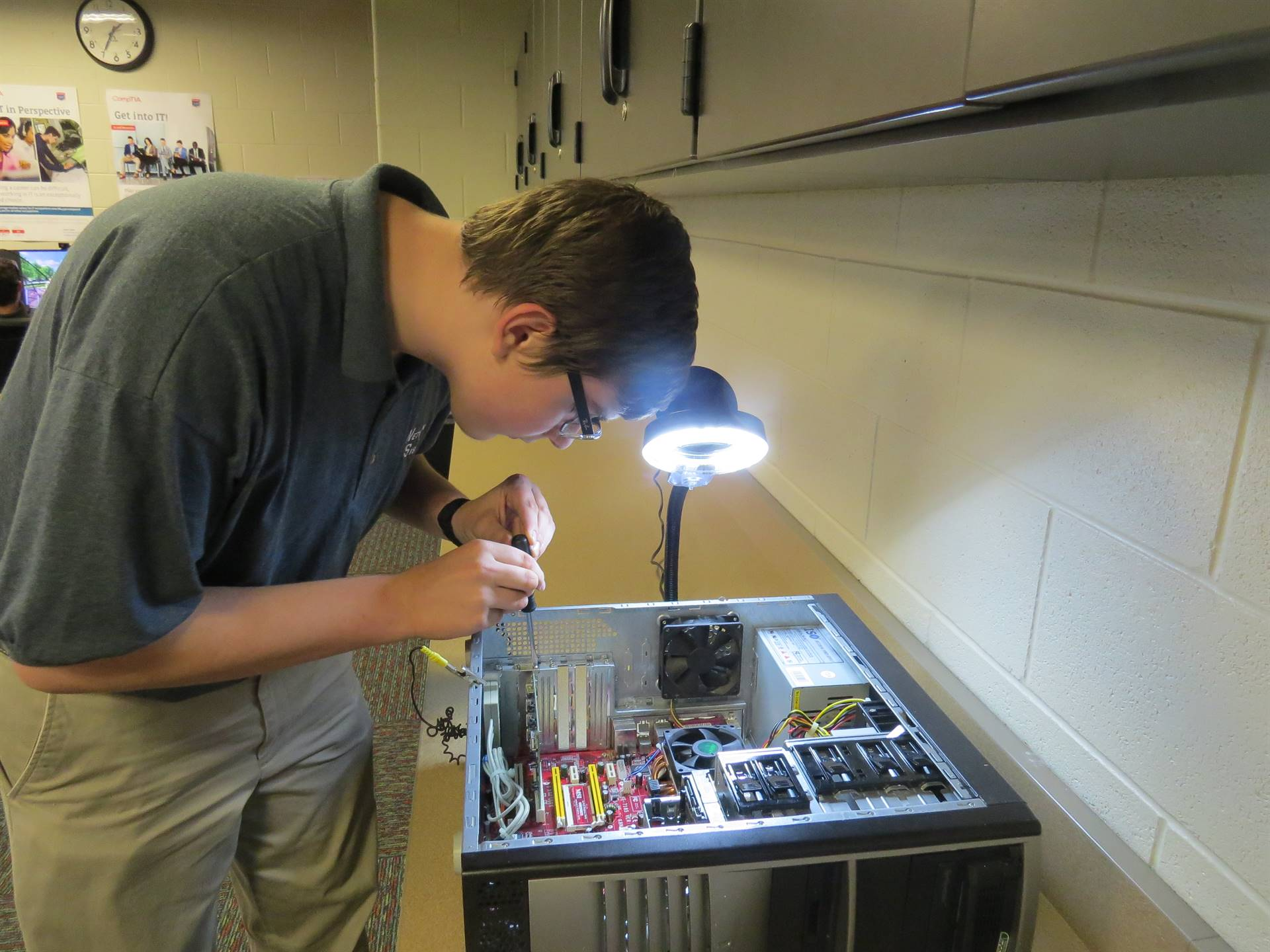 Male student repairing internal components of a computer