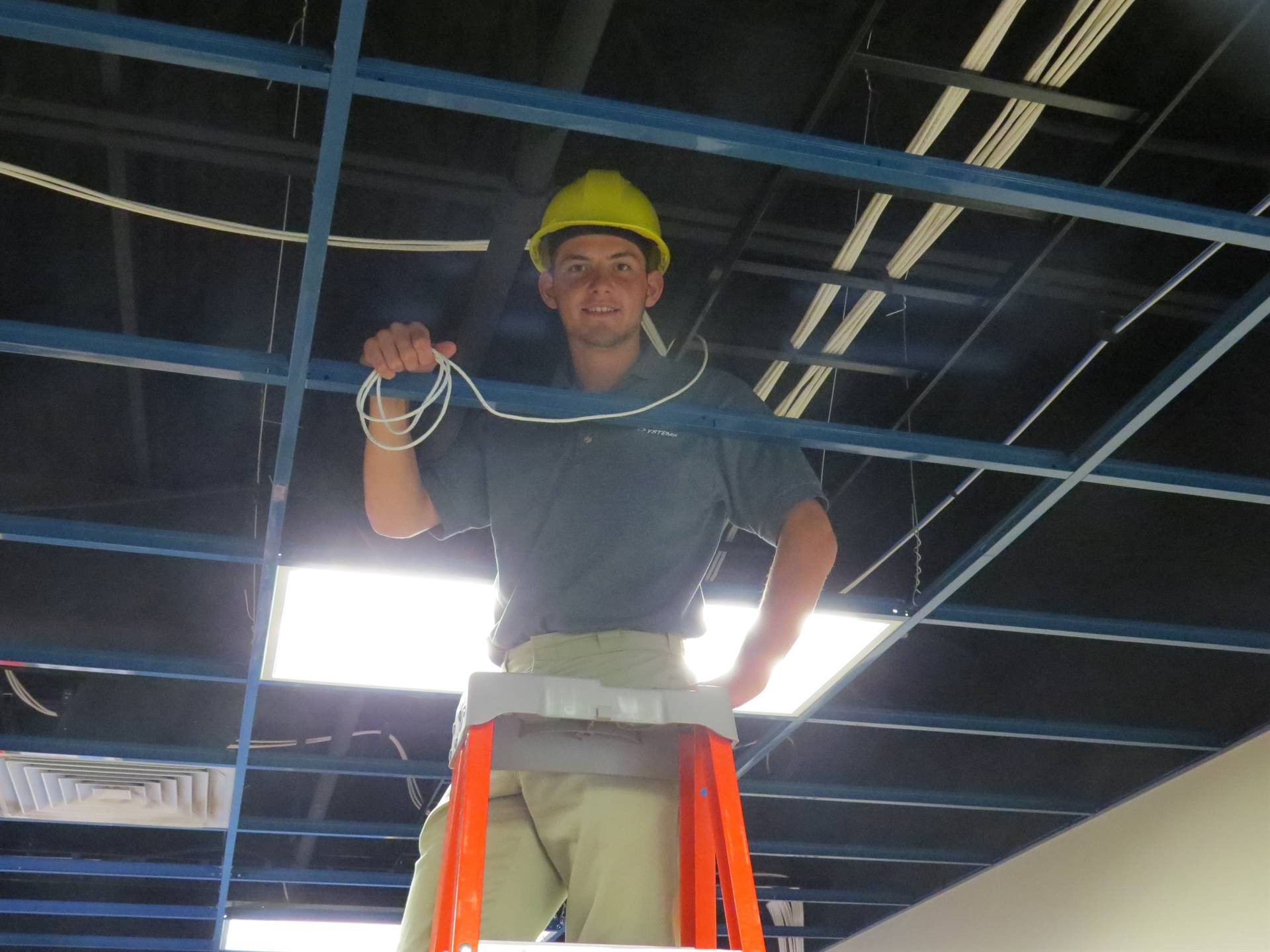 Male student in a yellow hard hat on a ladder installing computer wiring in the ceiling