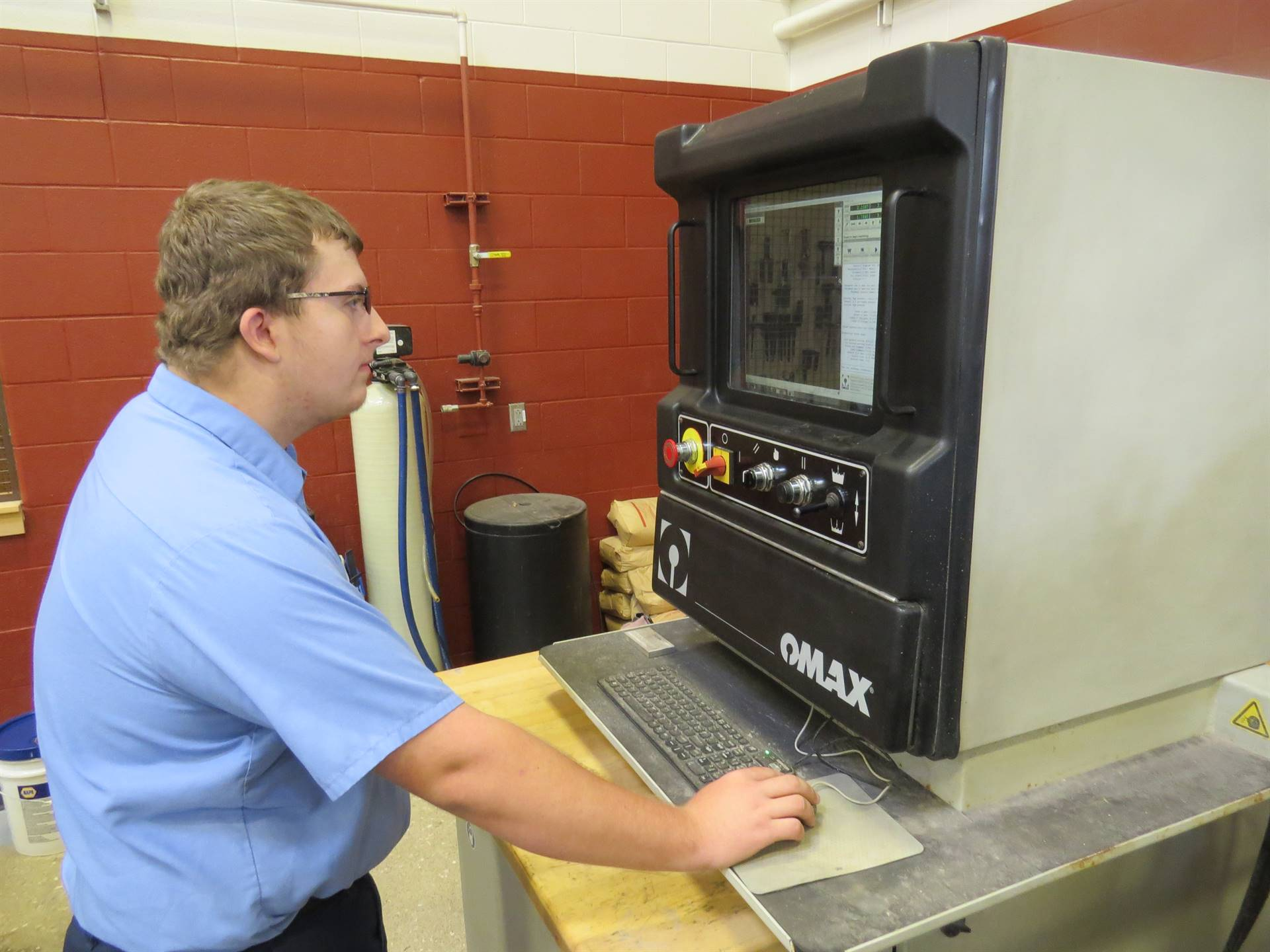 Male student programming the water jet