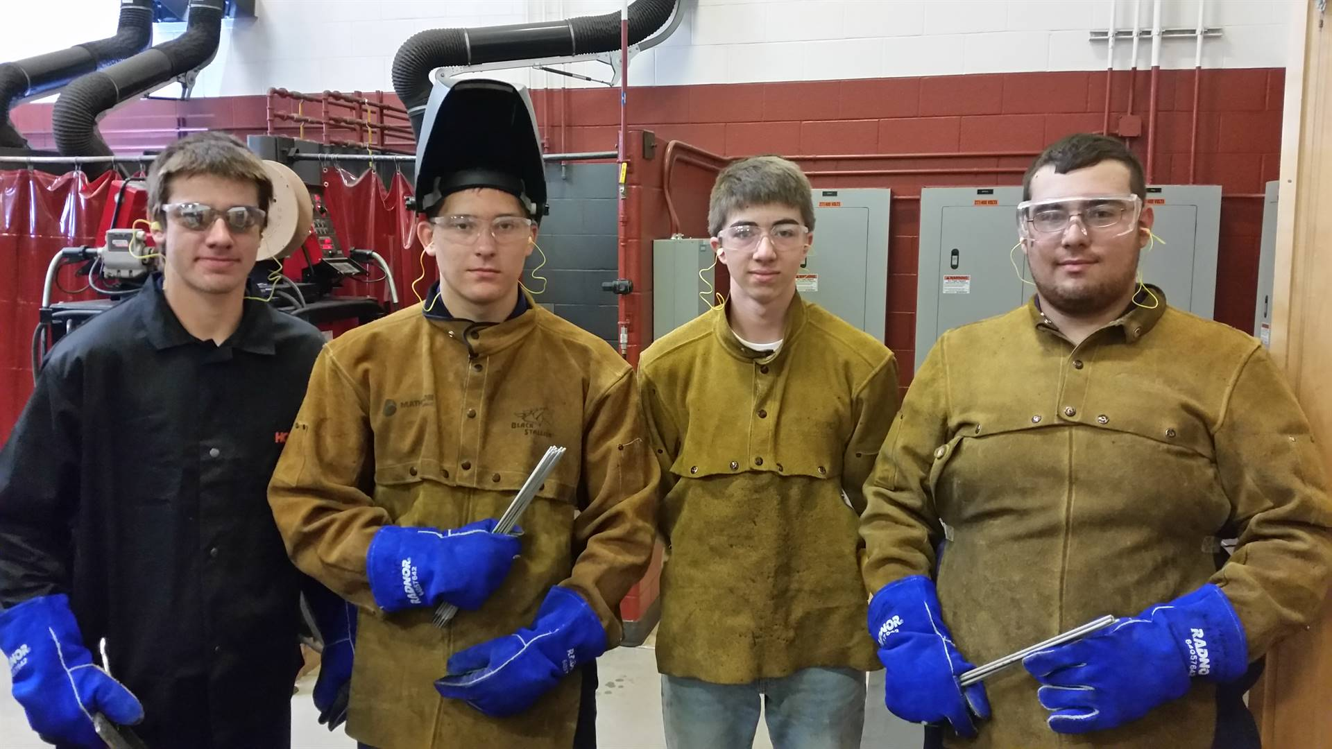 Four male Welding students in protective leather jackets and gloves