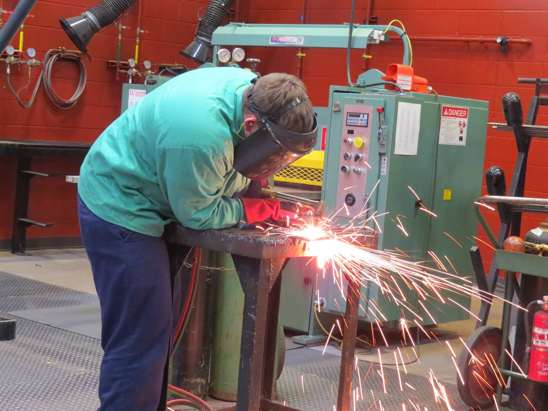 Male student cutting metal with sparks flying