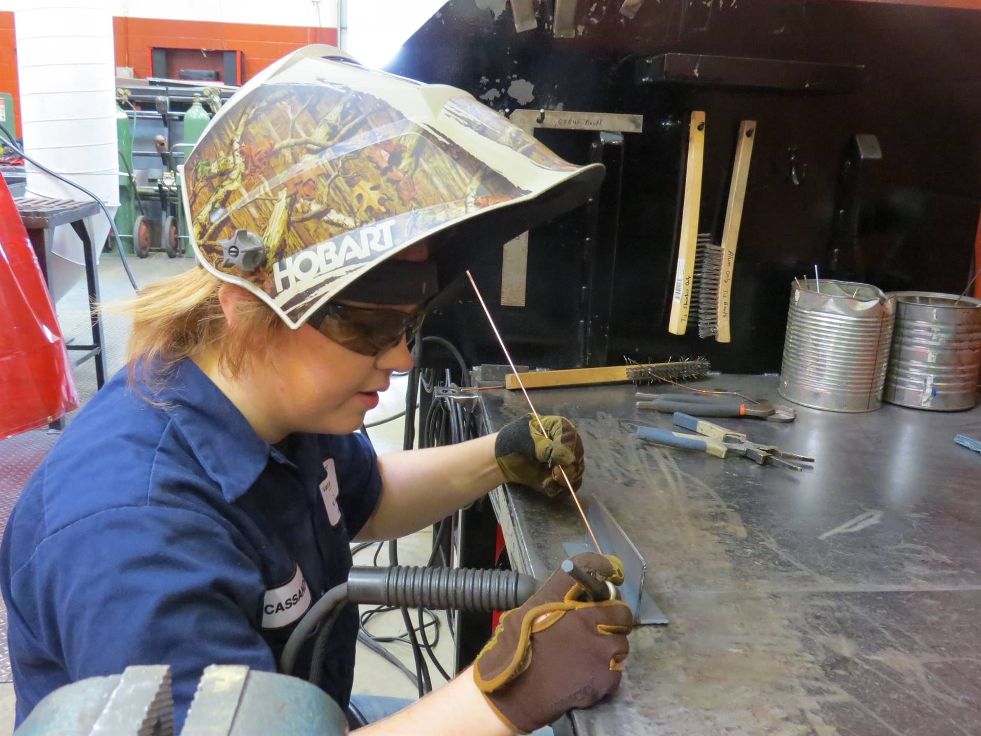 Female Welding student in camouflage welding helmet preparing to weld
