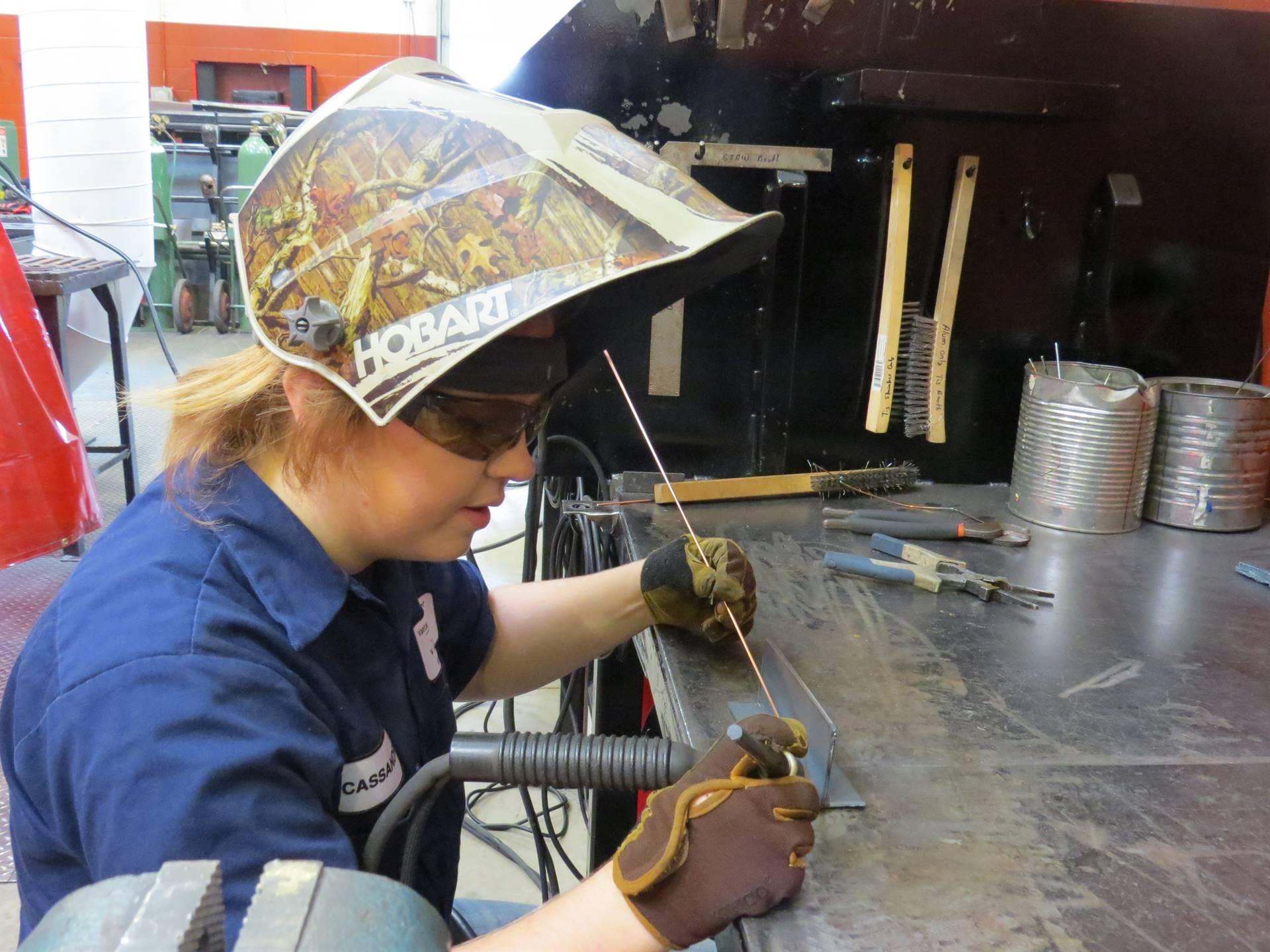 Female Welding student in camouflage welding helmet preparing to weld