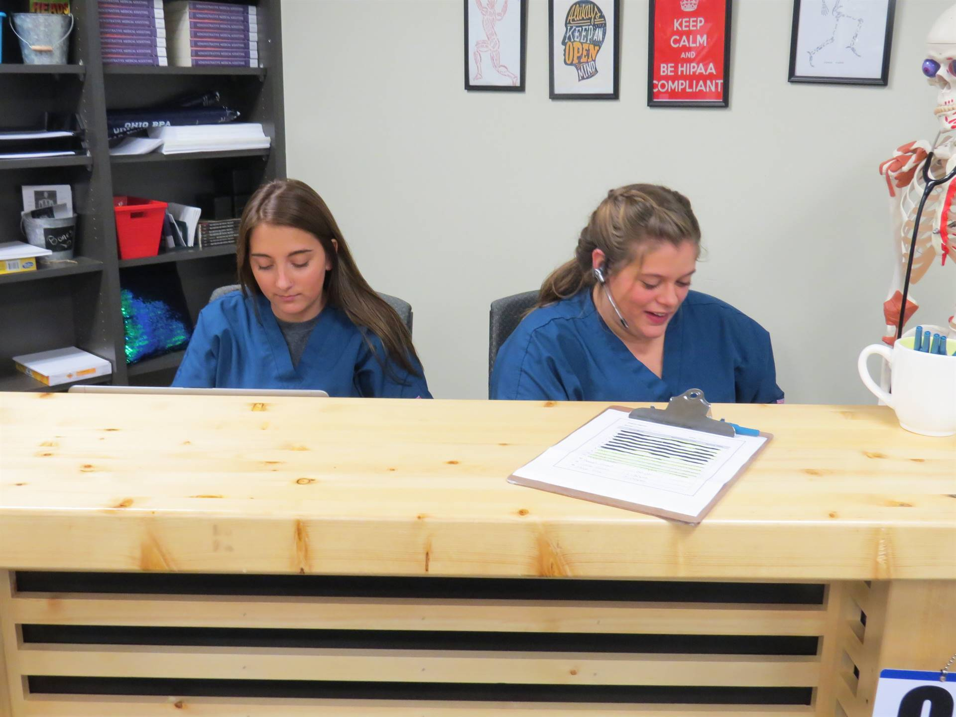 Two female students working the reception desk