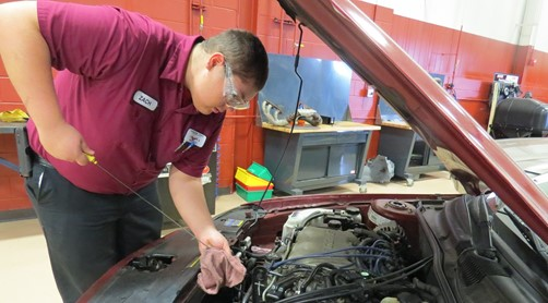 Student checking oil under car hood