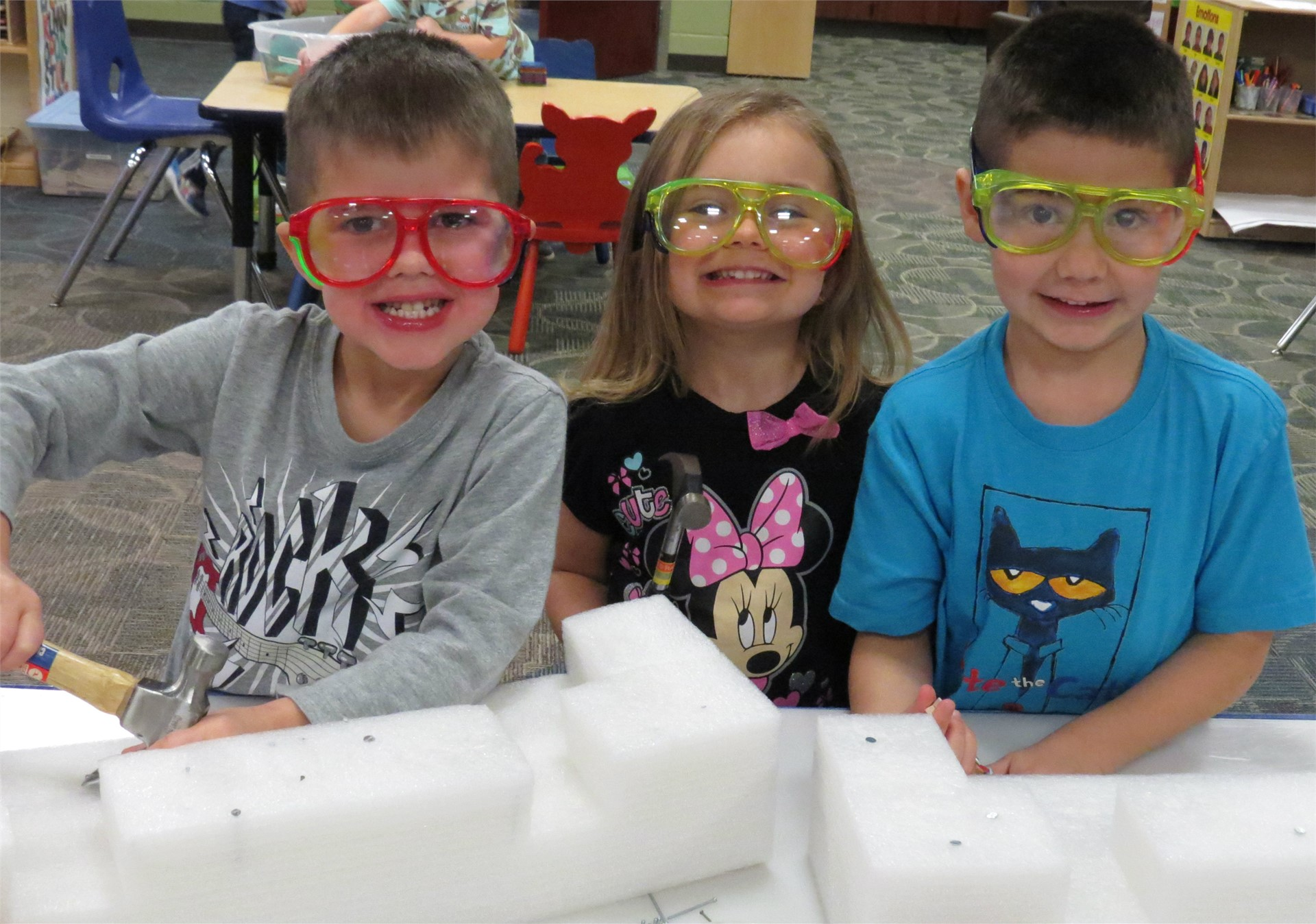 Smiling preschoolers wearing big, colorful safety glasses