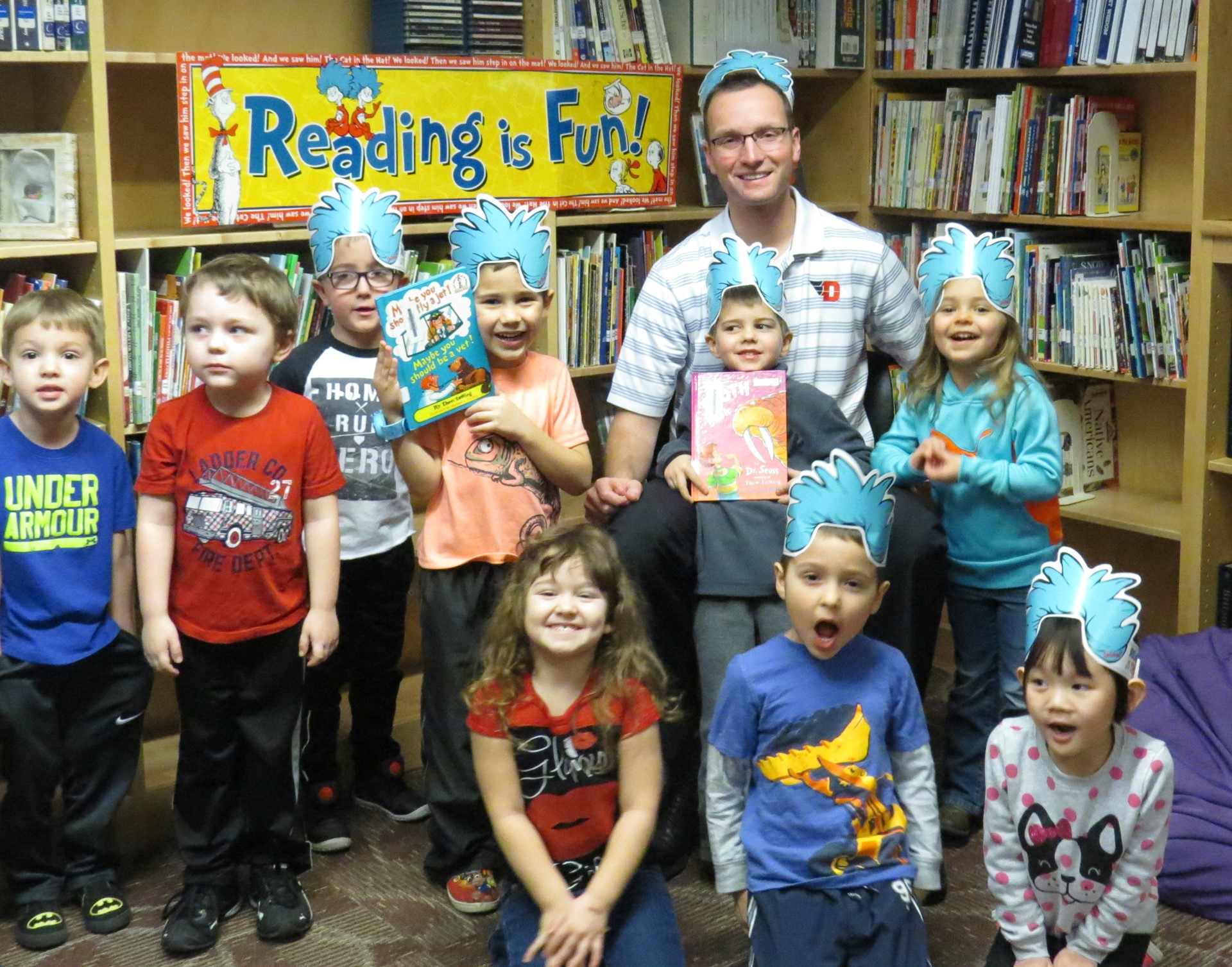 High School Director Mr. Unverferth with preschool students in the library wearing Dr. Seuss hats