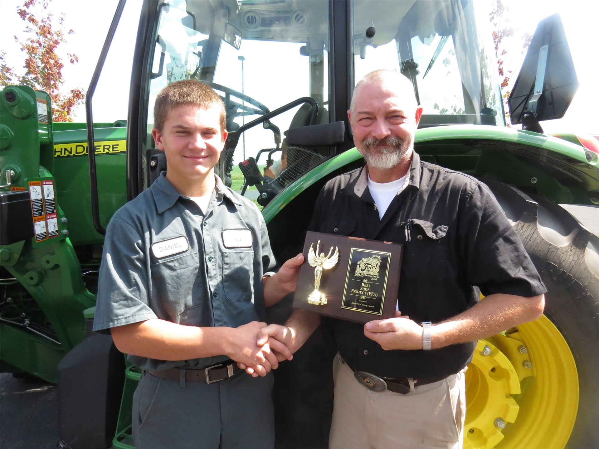 Male Ag student receiving a plaque from his teacher in front of a green tractor
