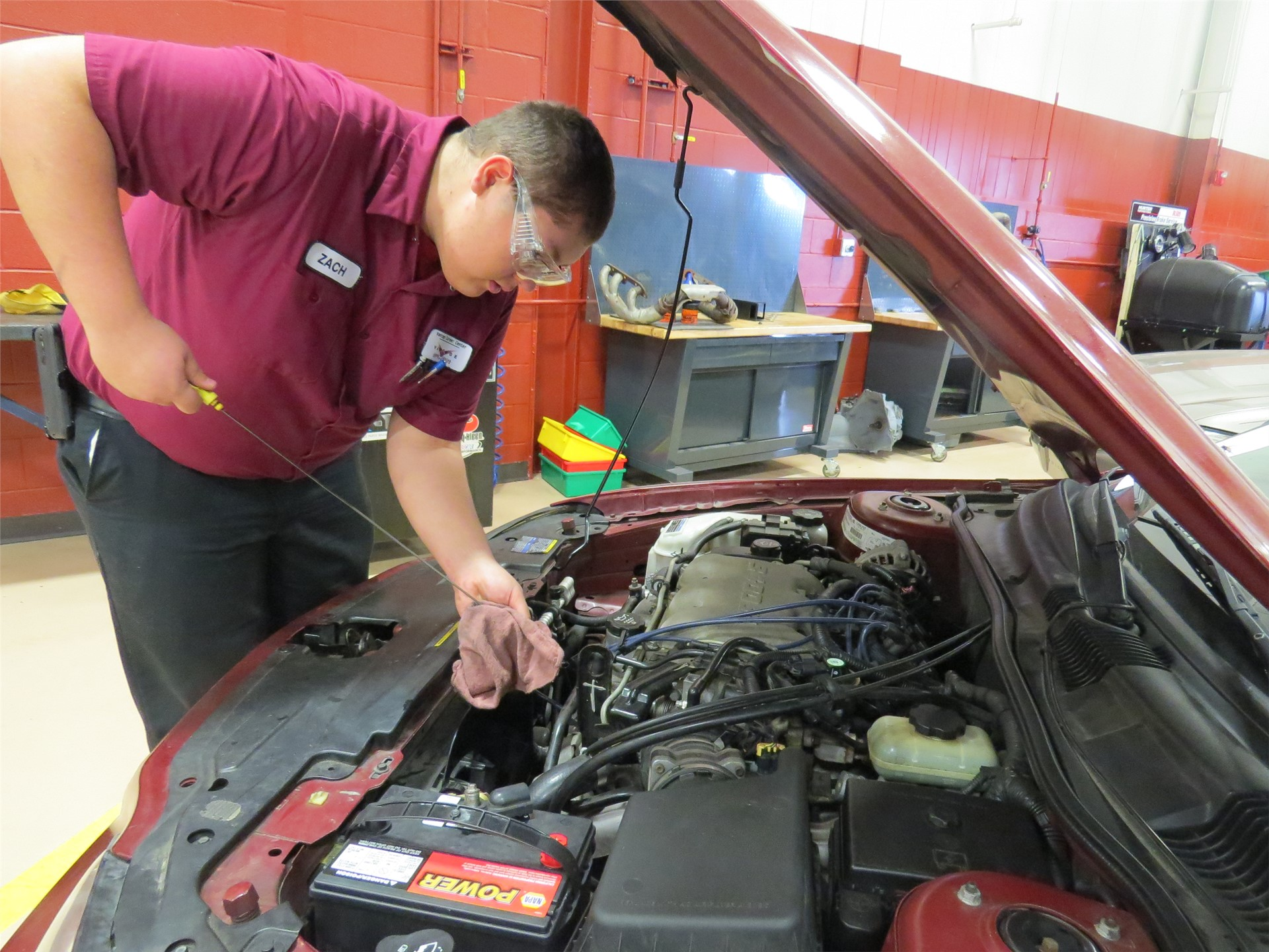 Male Auto Tech student checking oil under the hood of a car